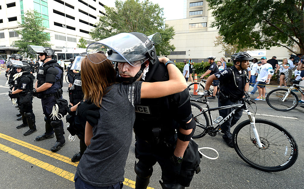A woman hugs a police officer outside Bank of America Stadium on Sept. 25, 2016 in Charlotte, N.C.