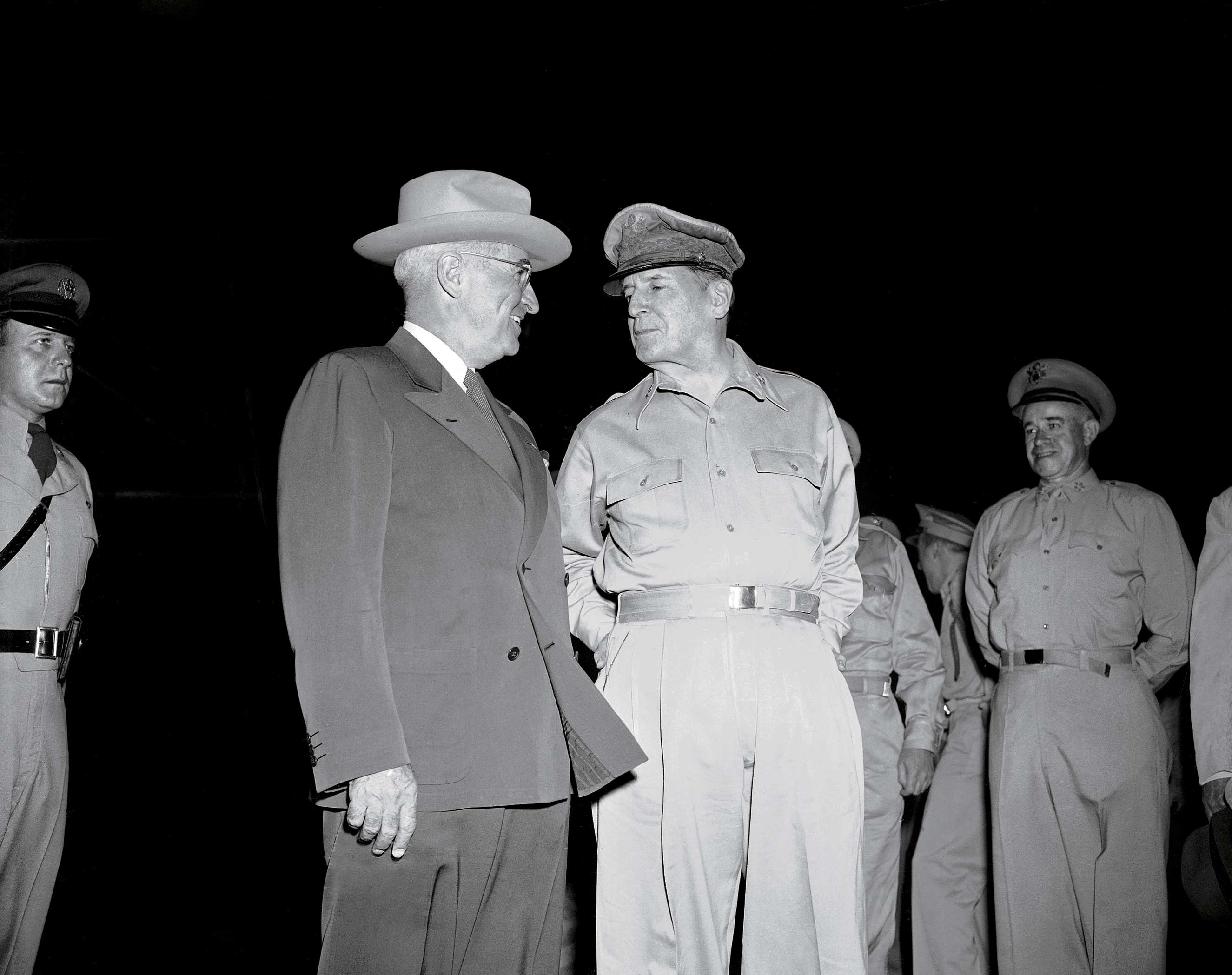 A smiling President Harry Truman is greeted by Gen. Douglas MacArthur after stepping from his plane on Wake Island where he went to confer with the general on Oct. 15, 1950.