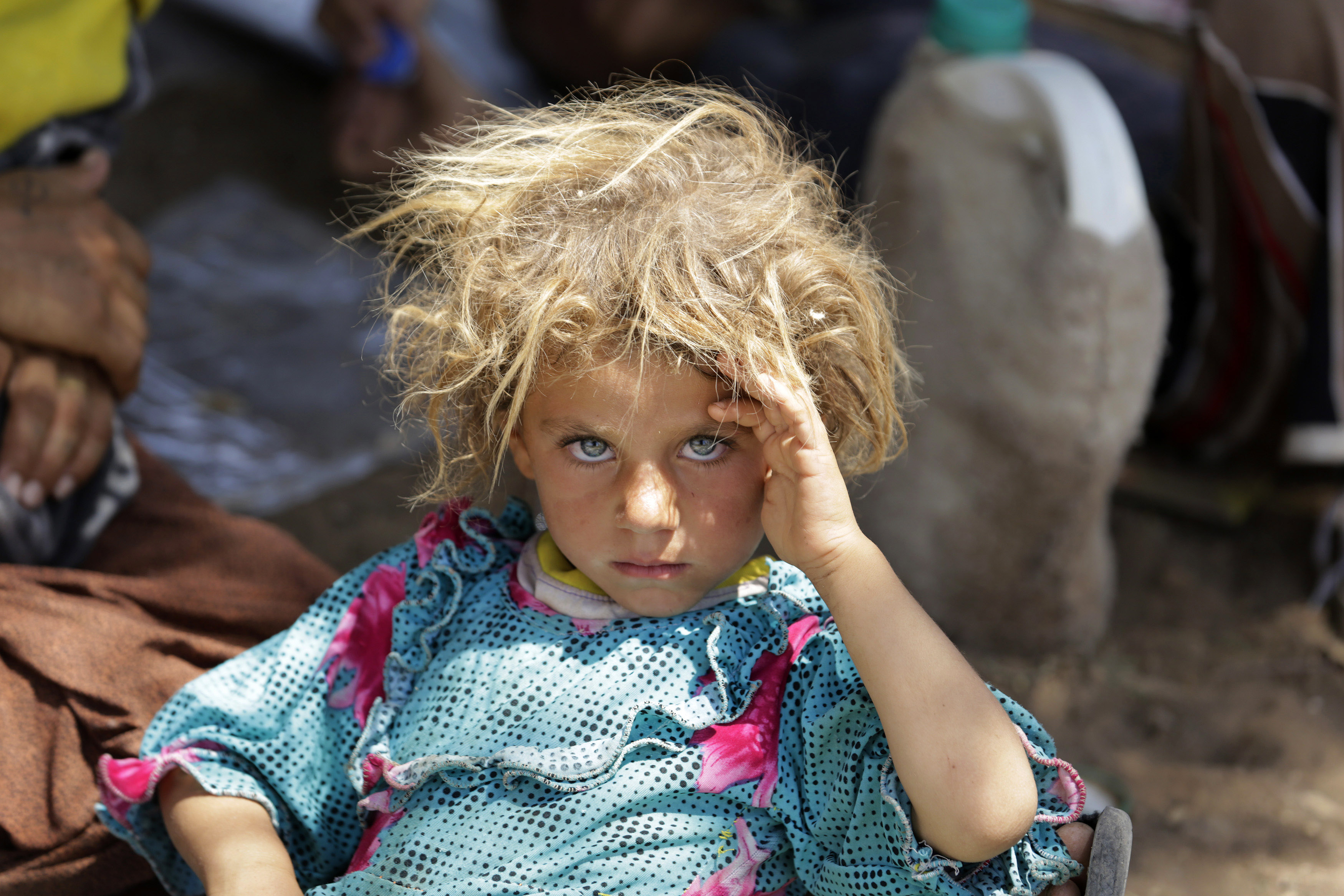 A girl from the minority Yazidi sect, fleeing the violence in the Iraqi town of Sinjar, rests at the Iraqi-Syrian border crossing in Fishkhabour, Dohuk province on August 13, 2014.