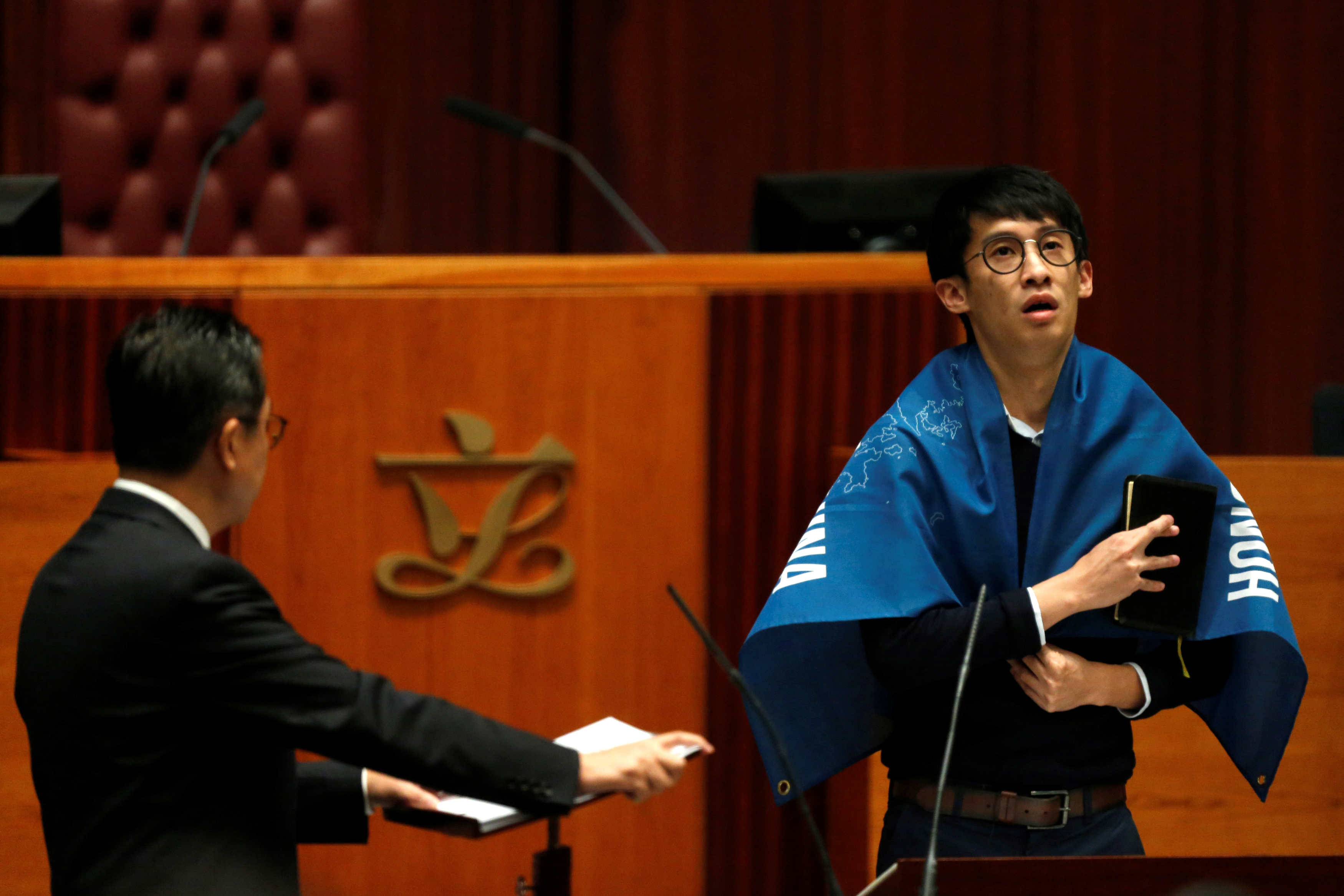 Newly elected lawmaker Sixtus  Baggio  Leung, right, wraps himself in a banner that says  Hong Kong Is Not China  while taking oath at the Legislative Council in Hong Kong on Oct. 12, 2016