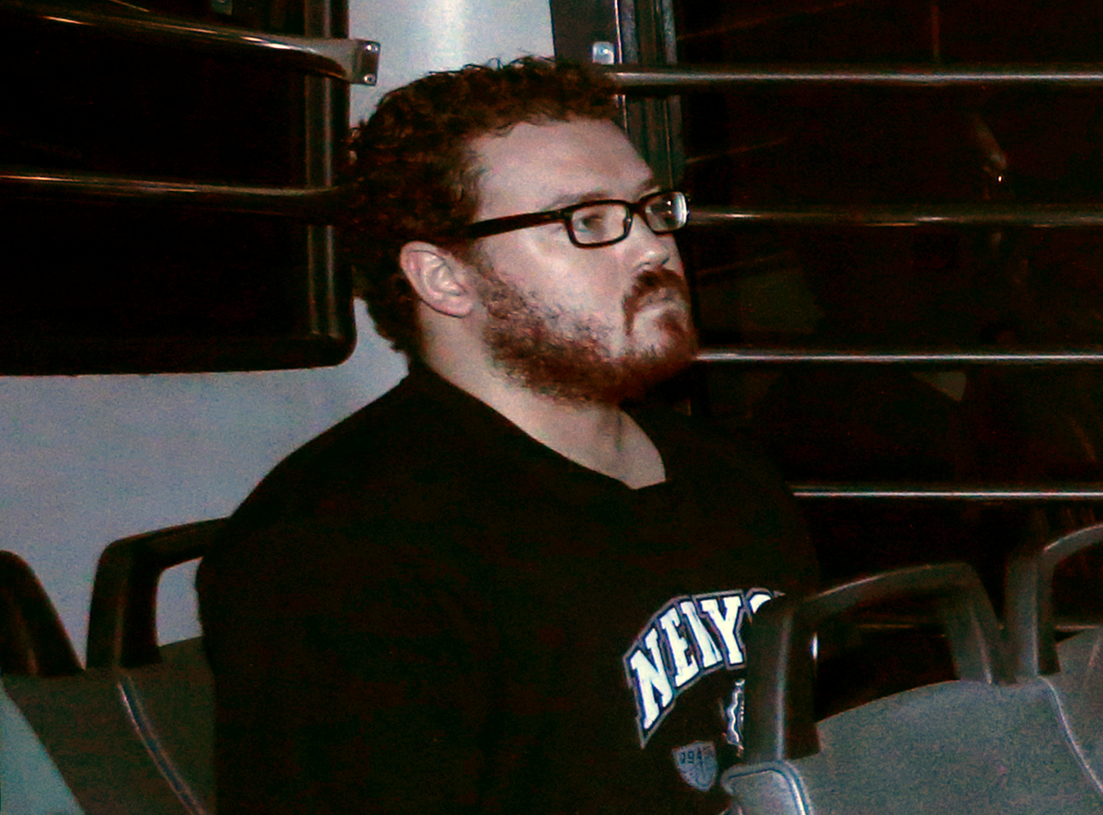 Rurik George Caton Jutting, a British banker charged with two counts of murder after police found the bodies of two women in his apartment, sitting in the back row of a prison bus as he arrives at the Eastern Law Courts in Hong Kong on Nov. 24, 2014