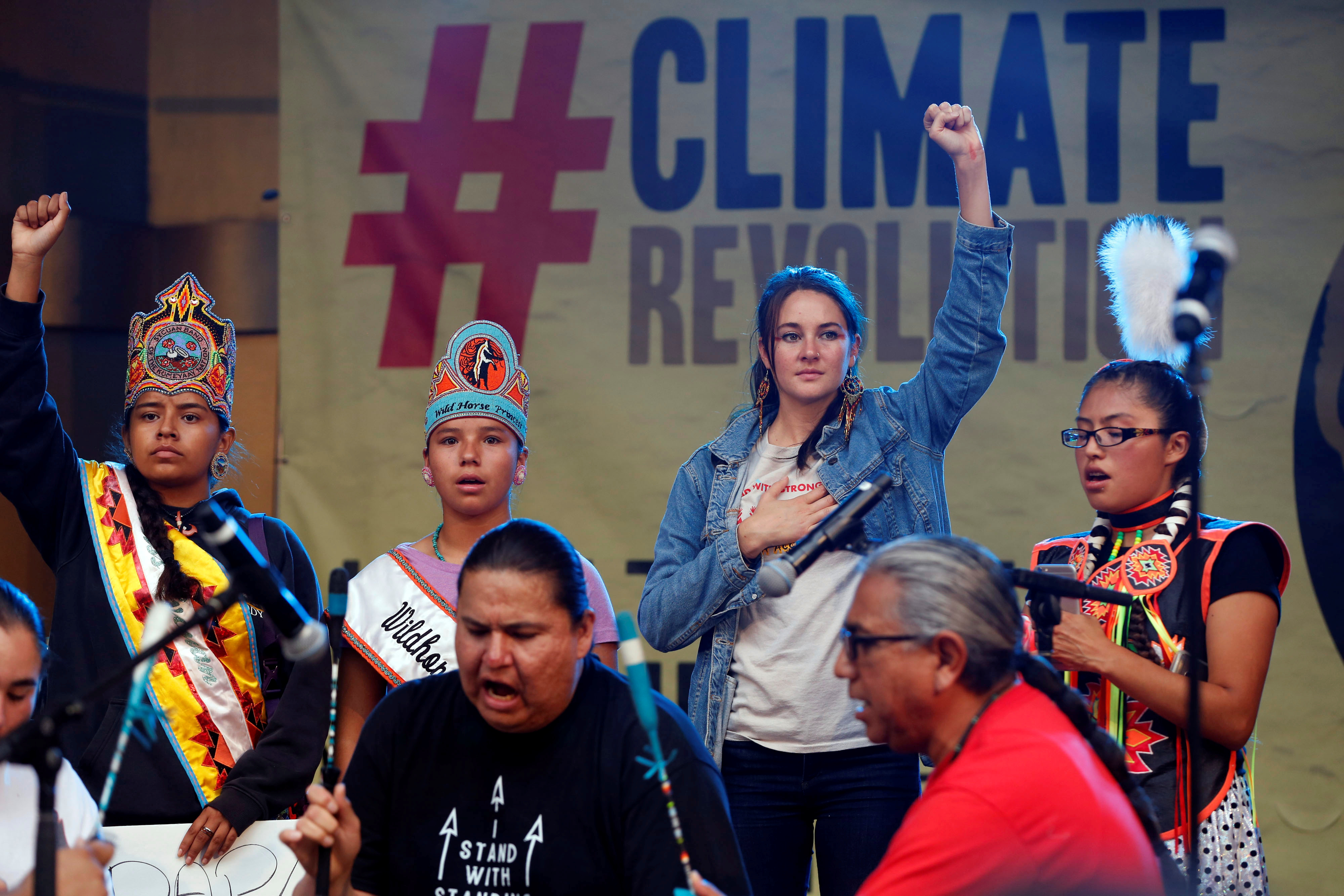 Actor Shailene Woodley stands with Native Americans on stage during a climate change rally in solidarity with protests of the pipeline in North Dakota at MacArthur Park in Los Angeles, California Oct. 23, 2016.