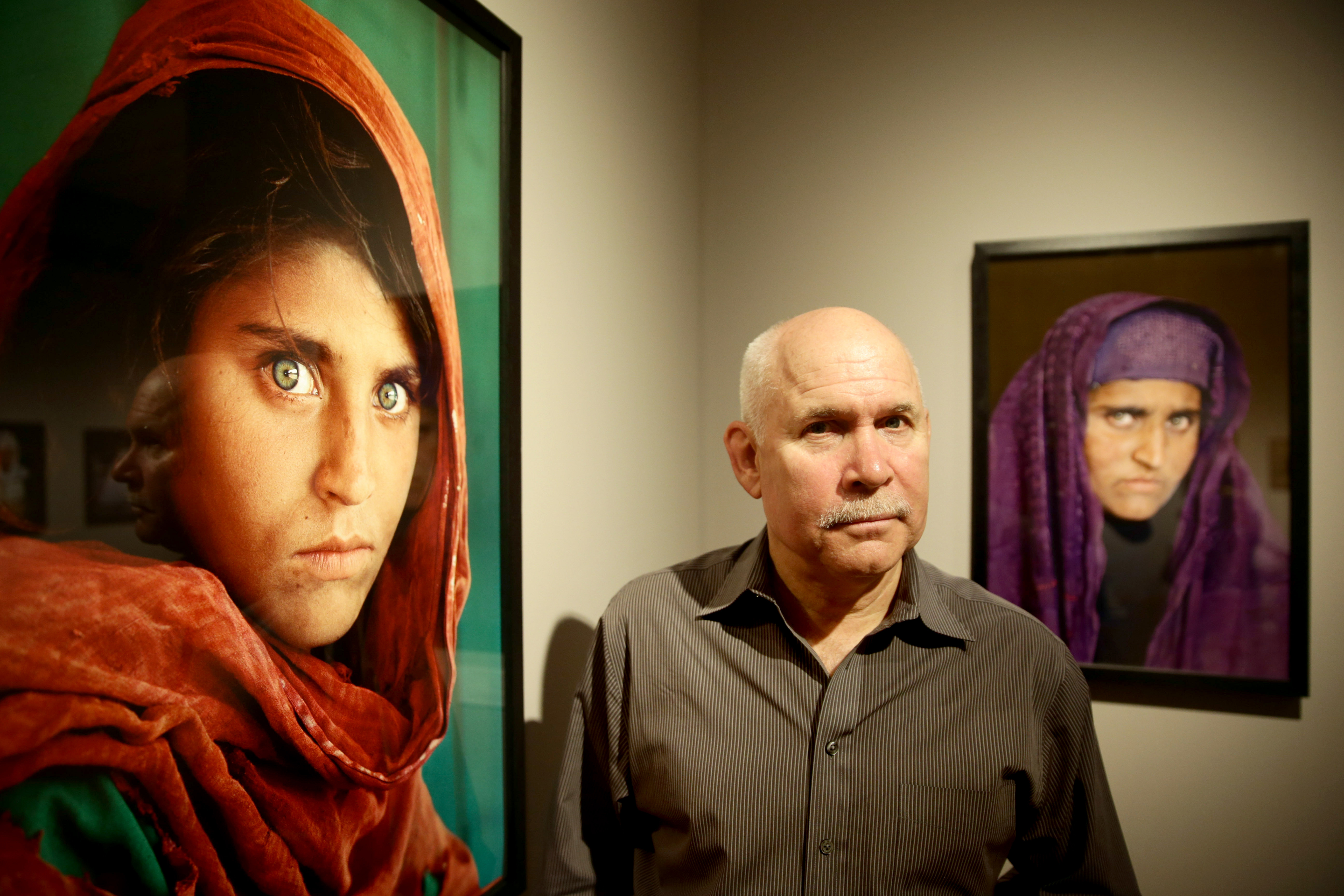 Steve McCurry poses next to his photos of the  Afghan Girl  named Sharbat Gula in Hamburg, Germany, on June 27, 2013.