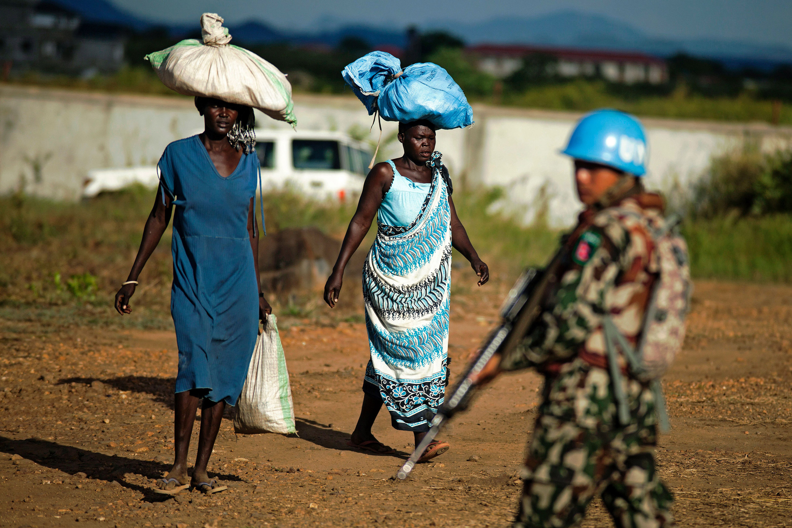 Displaced women carry goods as a Nepalese peacekeeper from the United Nations Mission in South Sudan (UNMISS) patrols outside the premises of the UN Protection of Civilians (PoC) site in Juba on Oct. 4, 2016.