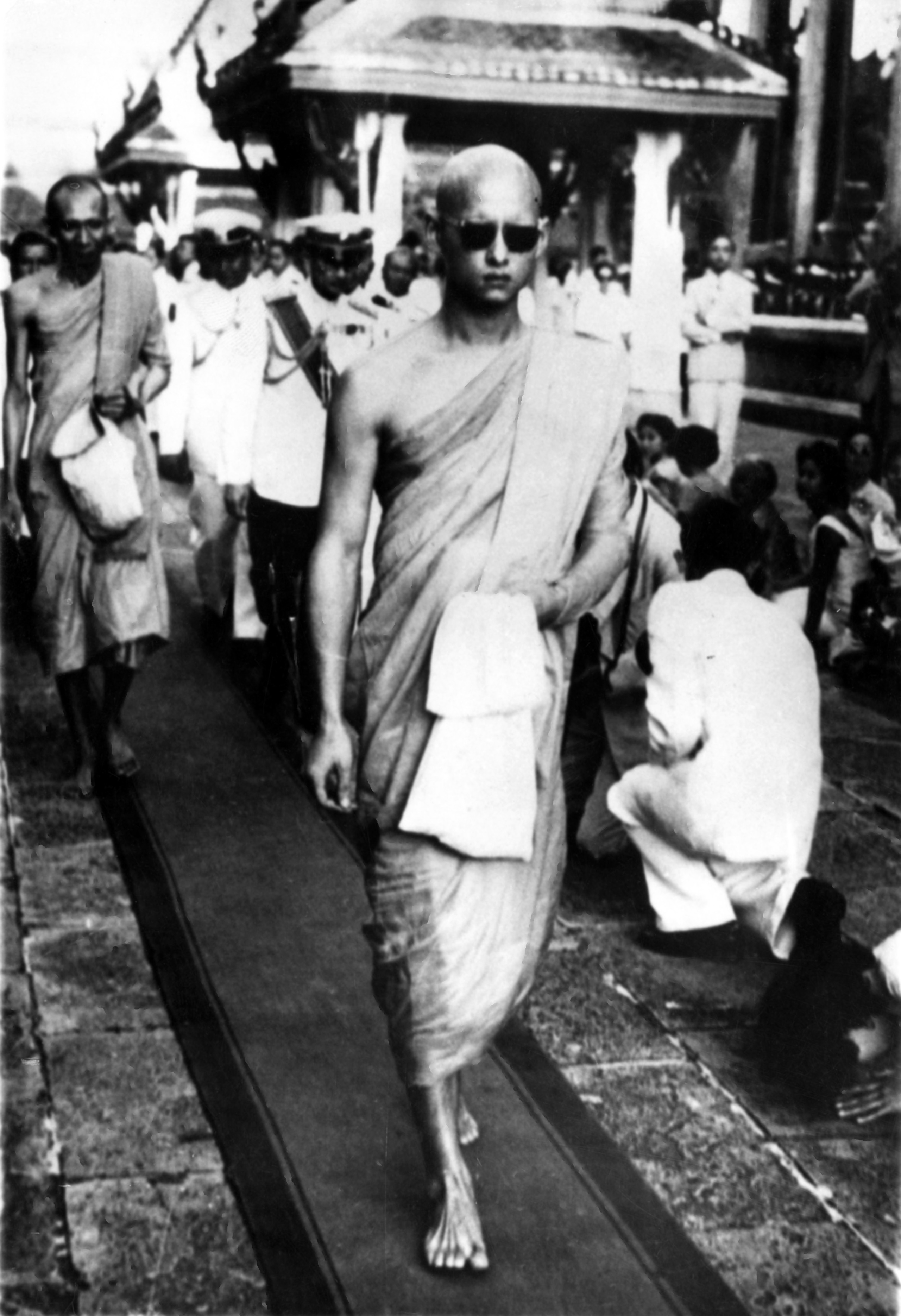 King Bhumibol Adulyadej, with head shaven and wearing the yellow robes of a monk, leaves a buddhist temple in Bangkok after being ordained a monk for two weeks in 1956.