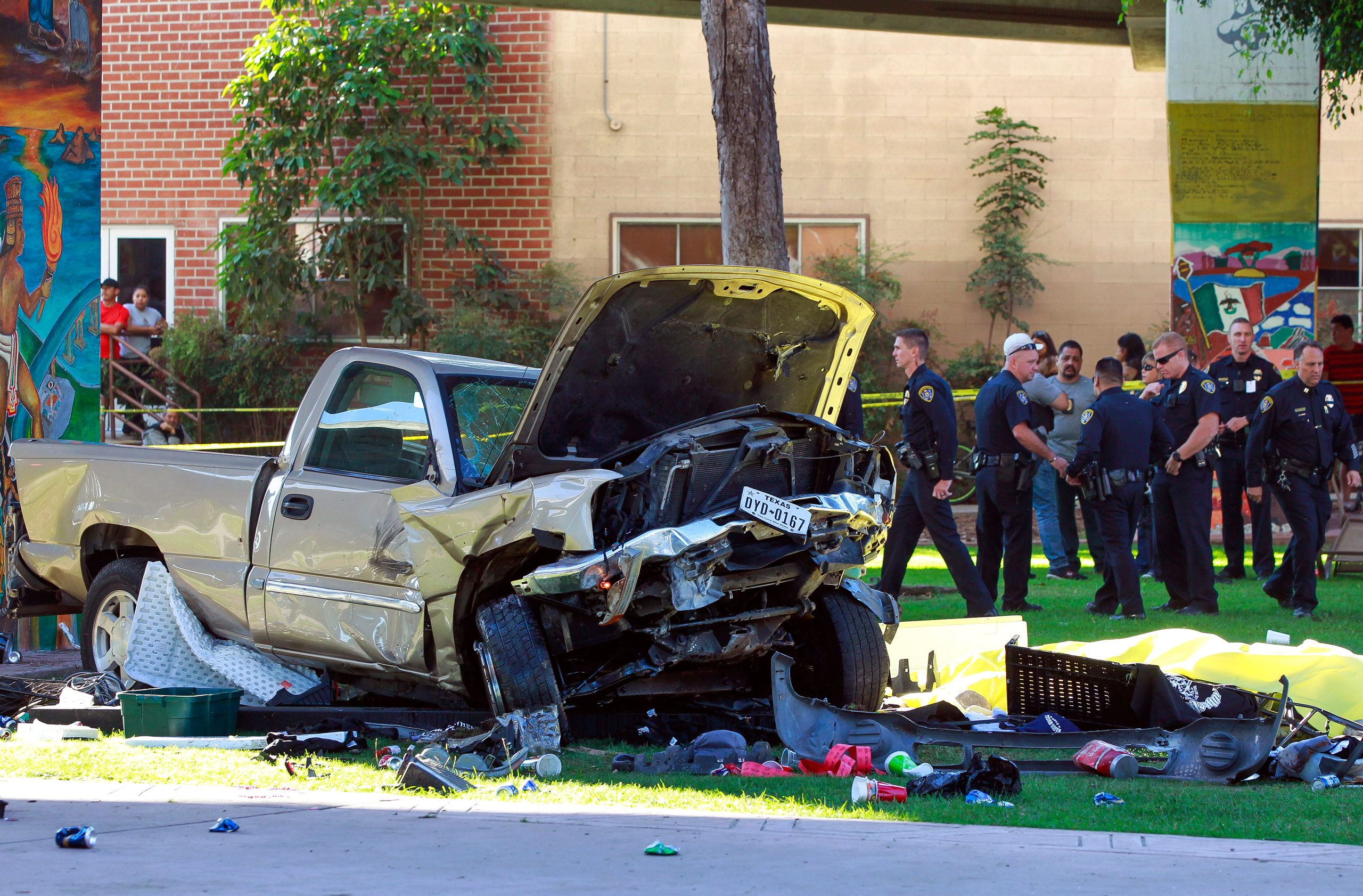 Police stand near the pickup truck that landed at Chicano Park after it flew off a ramp to the San Diego Coronado Bridge in San Diego on Oct. 15, 2016.