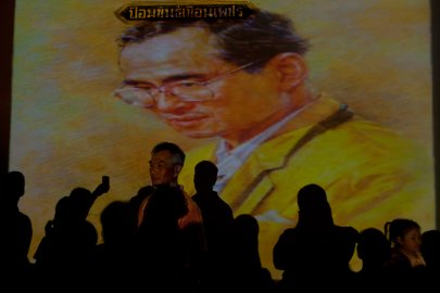 People in front of an image of King Bhumibol Adulyadej of Thailand during a celebration of his 84th birthday, Bangkok, Thailand, Dec. 5, 2011.