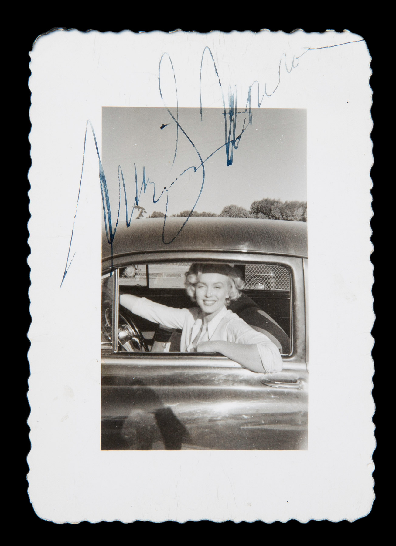 Marilyn Monroe driving a car and posing through the driver's side window, taken in the mid-1950s.