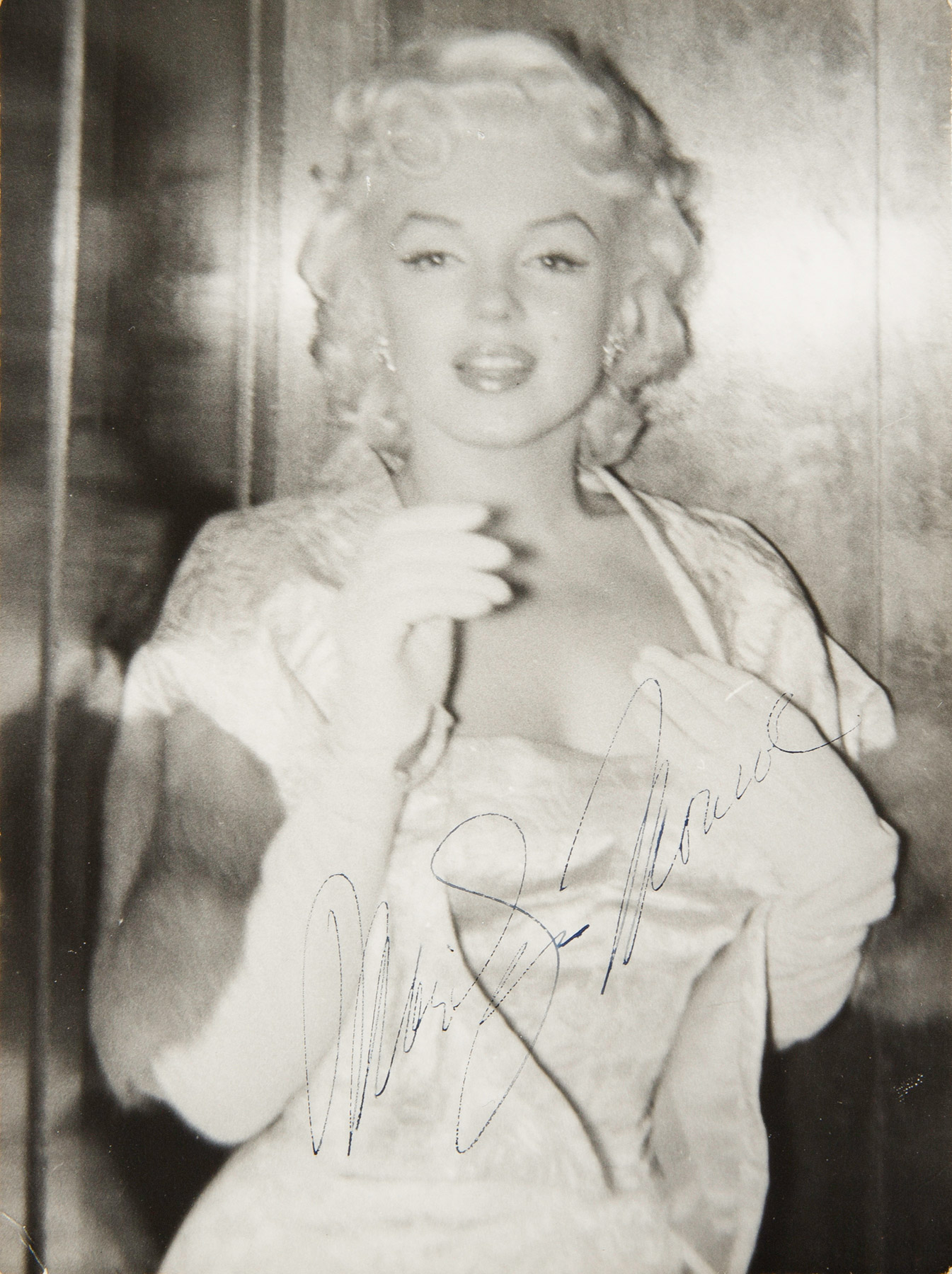 Marilyn Monroe wearing a white brocade gown with matching jacket and white evening gloves as she attended the New York City premiere of East of Eden on March 9, 1955.