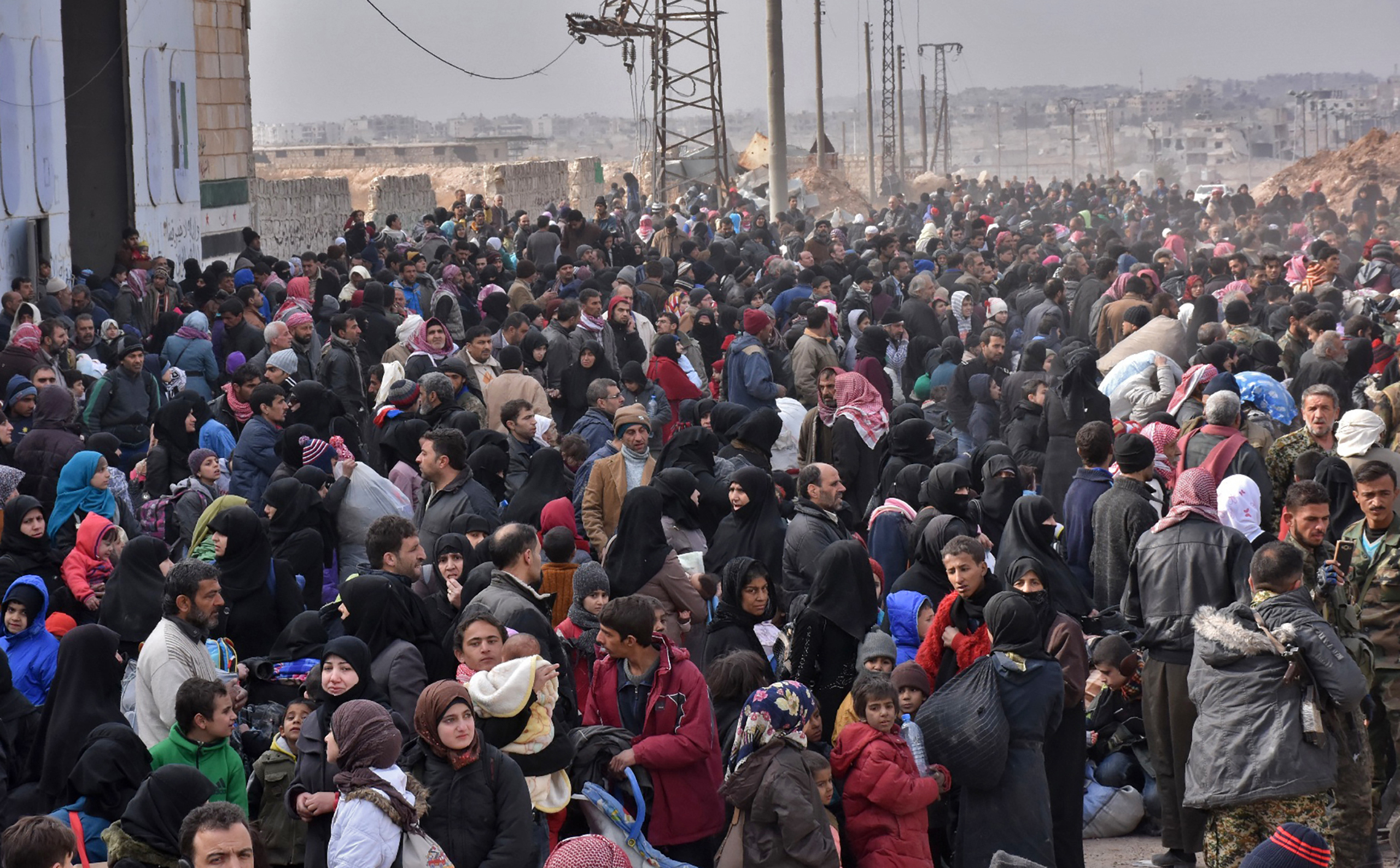 Syrian families, fleeing from various eastern districts of Aleppo, queue to get onto governmental buses in the government-held eastern neighborhood of Jabal Badro, before heading to government-controlled western Aleppo, on Nov. 29, 2016