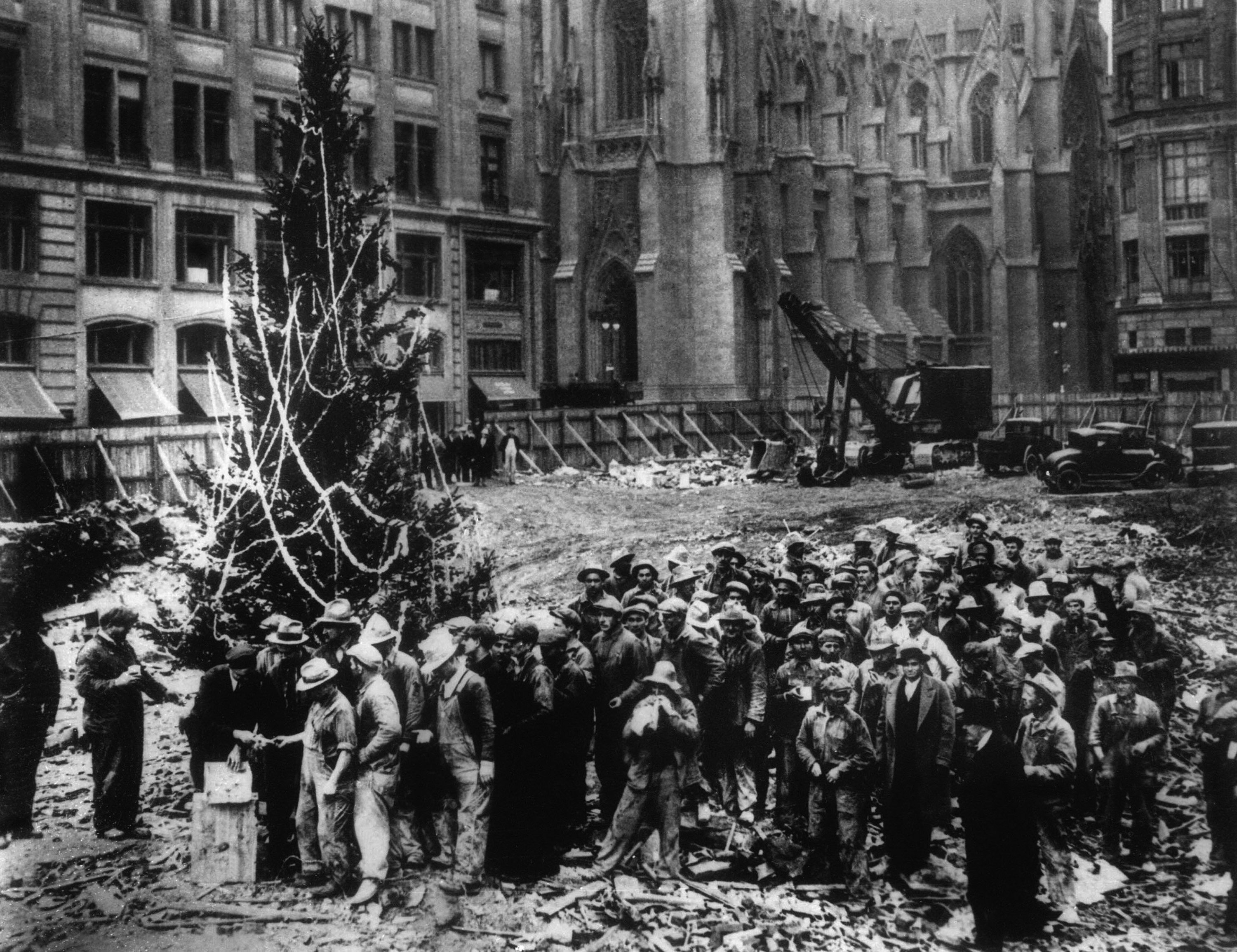 Construction workers line up for pay beside the first Rockefeller Center Christmas tree in New York in 1931. St. Patrick's Cathedral is visible in the background on Fifth Avenue.