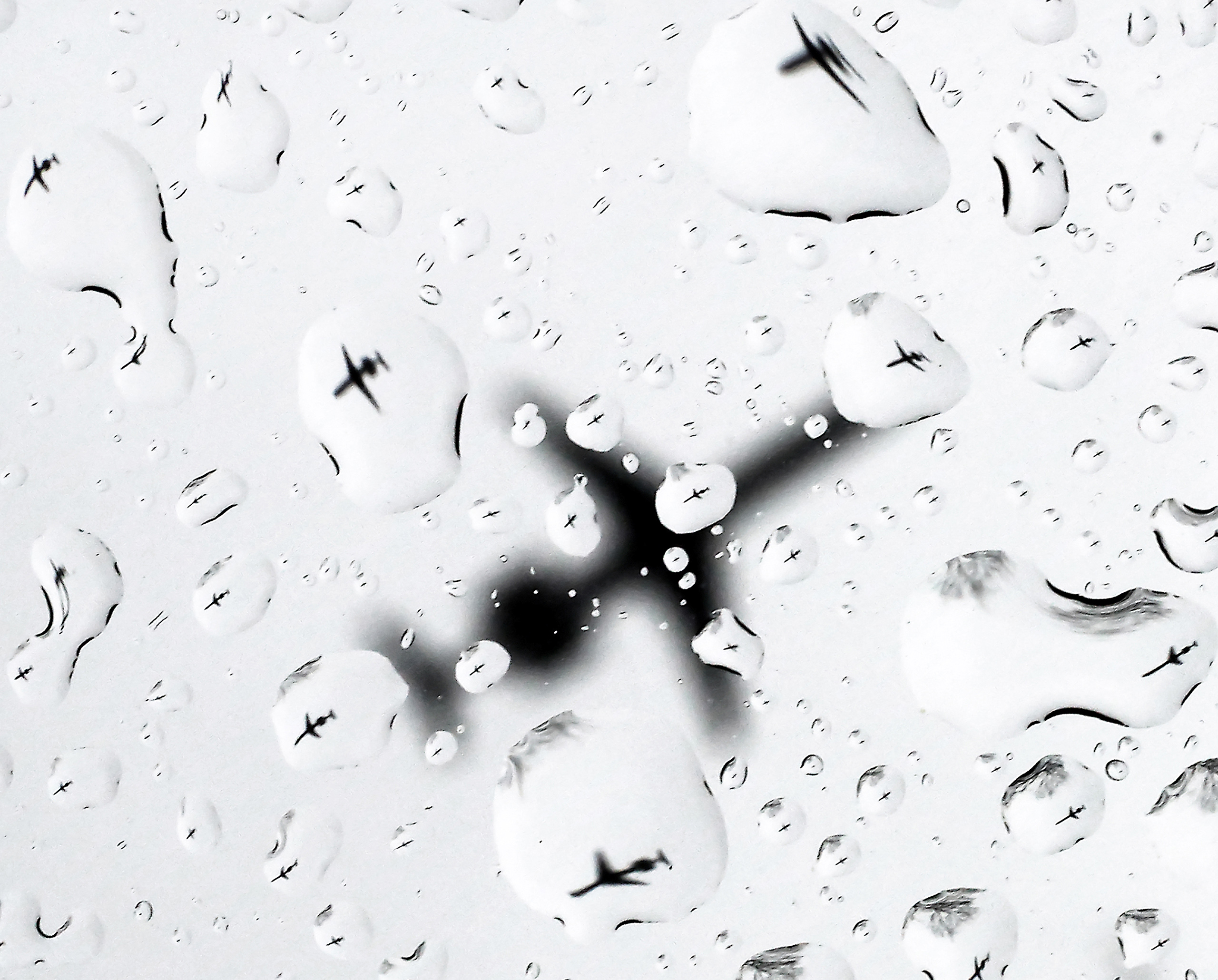 As a spring storm makes its way through the region, a plane is refracted in the raindrops on a vehicle window as it approaches the Dane County Regional airport in Madison, Wis., on March 23, 2016.