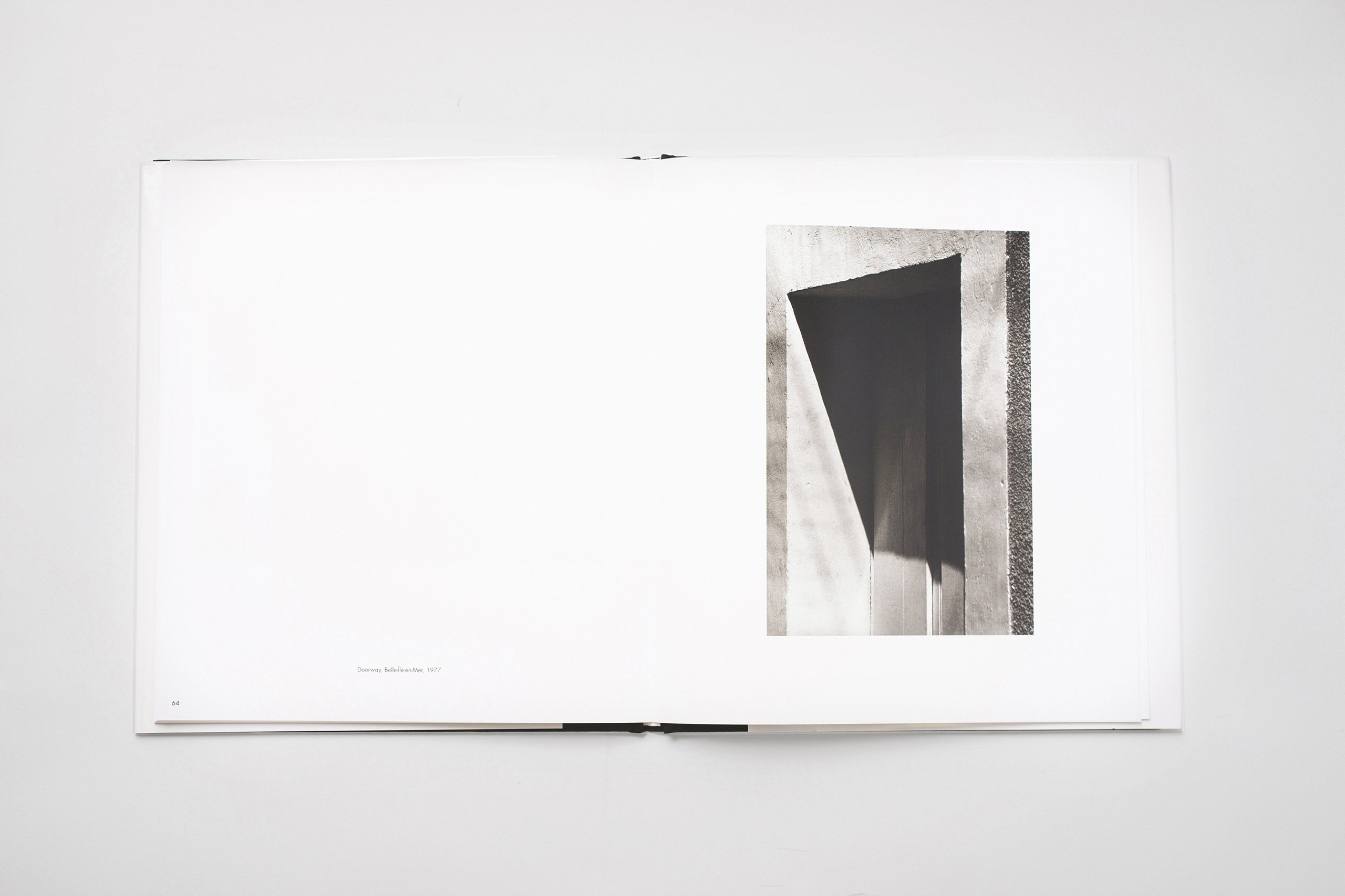 "Selected by writer and curator Vince Aletti:  In his introduction, Kelly writes that he started taking photographs in France in 1950, using the camera to ""make notations of things I had seen and subjects I had been drawing,"" which included branches, buildings, walls, doors, and windows. The earliest pictures in his book, which he compiled just before his death last December, look like drawings, but even as the work becomes more photographic, it remains flat, clean, and matter of fact in a style that recalls Edward Weston, Walker Evans, and the New Topographics crew. ""My photographs are simply records of my vision, how I see things,"" Kelly writes. ""My ideas develop from seeing, not from photographs."" Point taken, but seeing through Kelly's eyes can be revelatory. That diagonal shadow, that long flat roof, that newly repaired sidewalk square–all these found geometries suddenly look like Ellsworth Kellys."""
