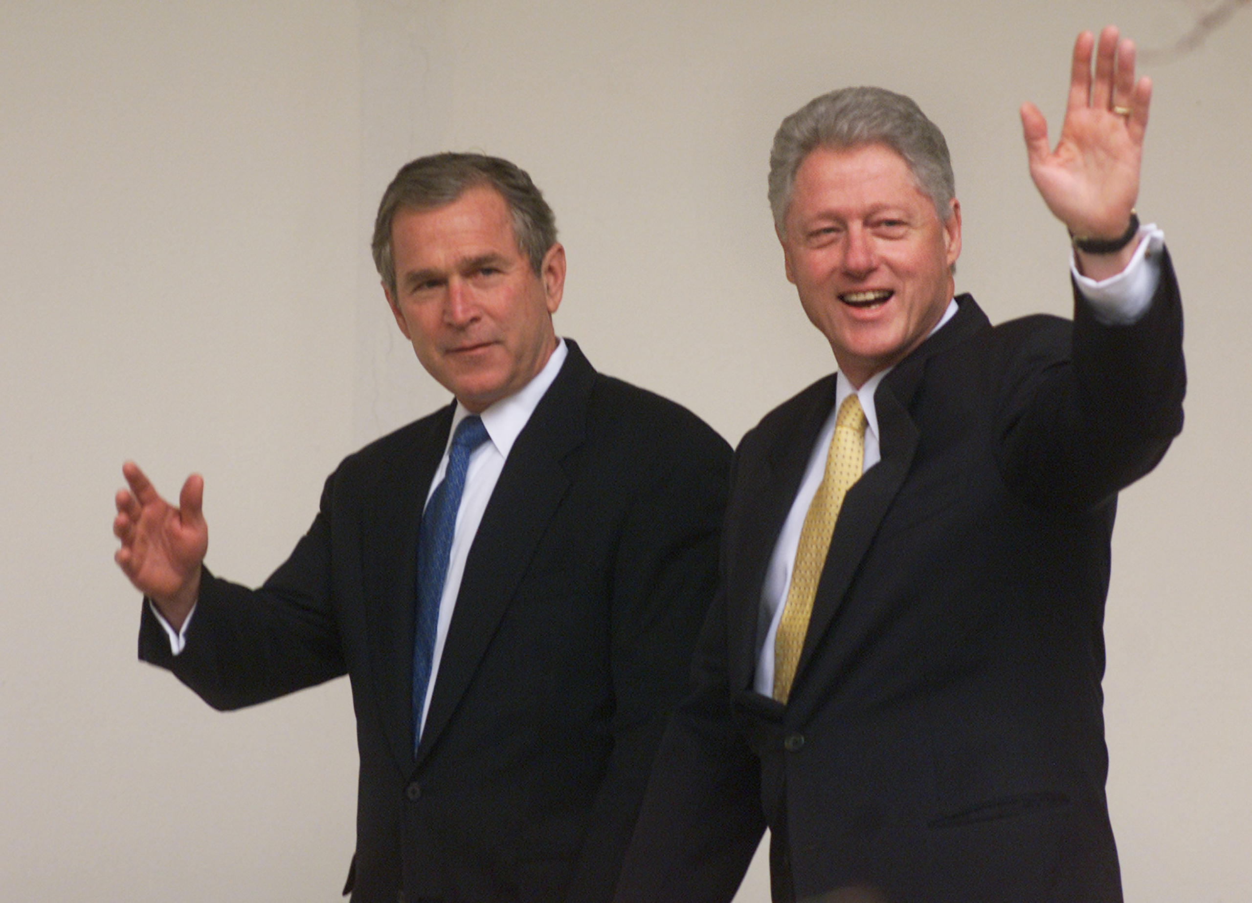 George W. Bush, left, and Bill Clinton wave before their meeting at the White House in Washington, D.C., on Dec. 19, 2000