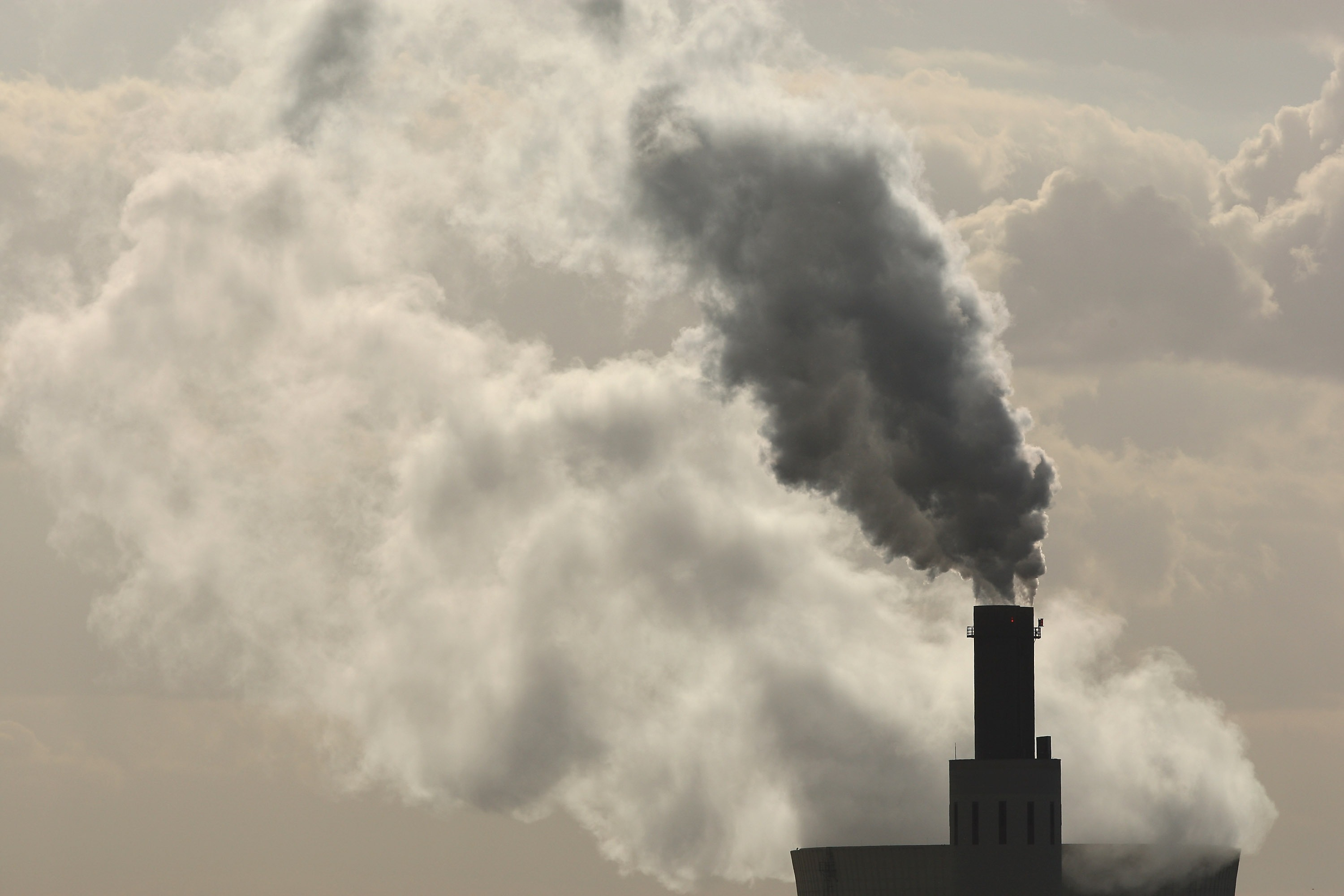 Exhaust rises from the main chimneys of the coal-fired power plant Heizkraftwerk Reuter West as steam rises from its cooling tower behind July 31, 2007 in Berlin, Germany