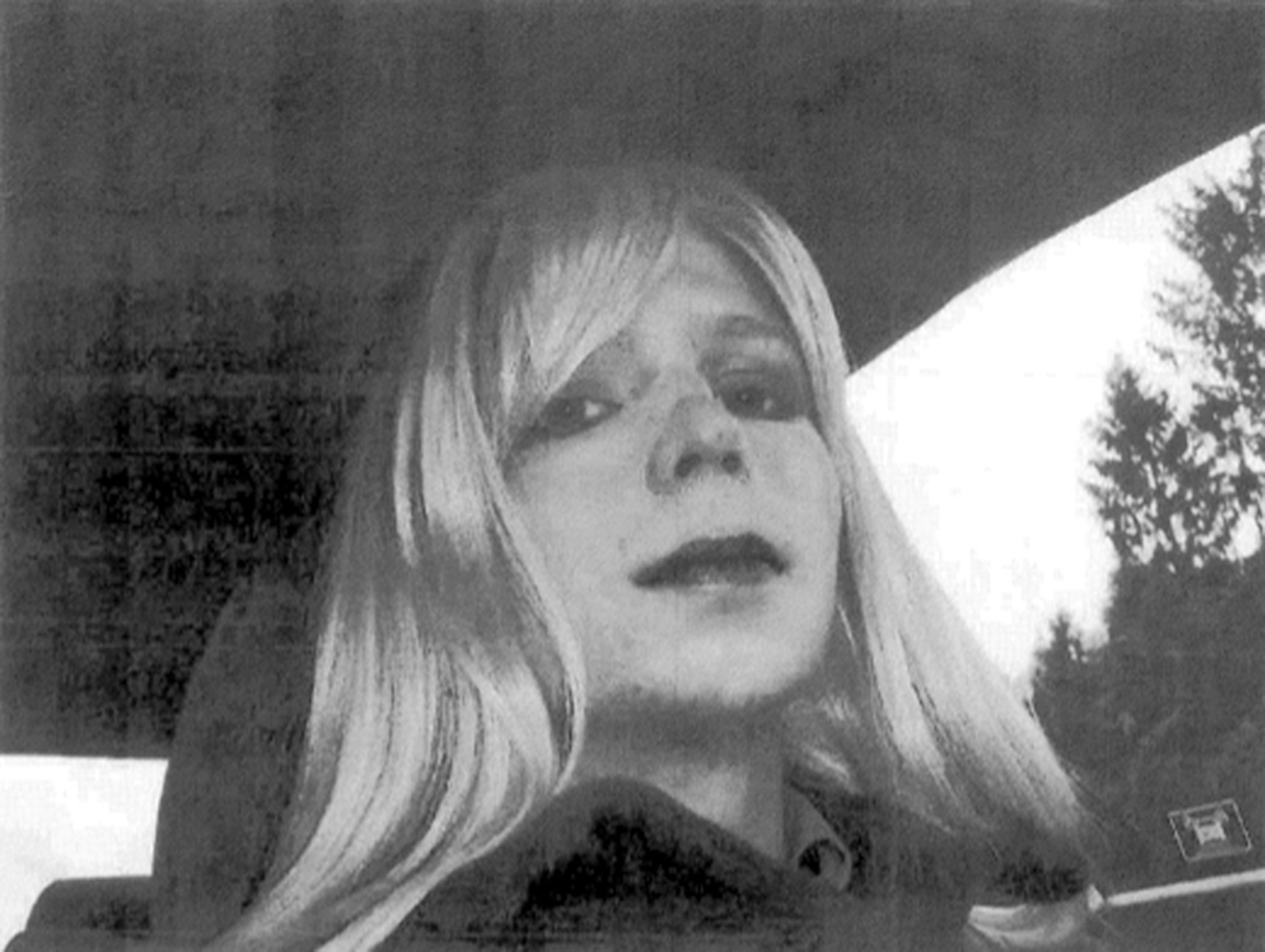 Chelsea Manning poses for a photo wearing a wig and lipstick.