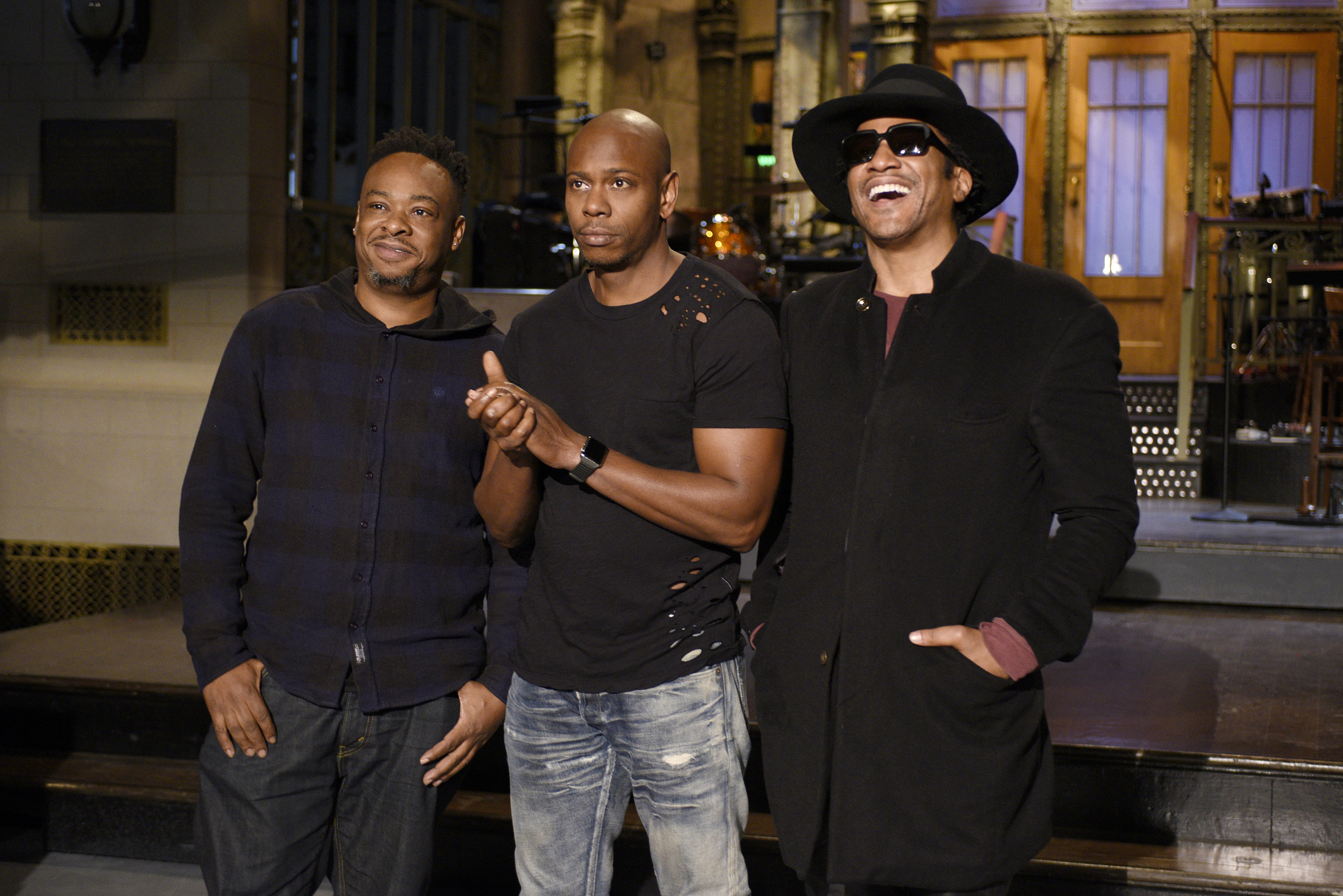 Pictured: (l-r) Jarobi White and Q-Tip of musical guest A Tribe Called Quest pose with host Dave Chappelle (center) on Nov. 10, 2016.