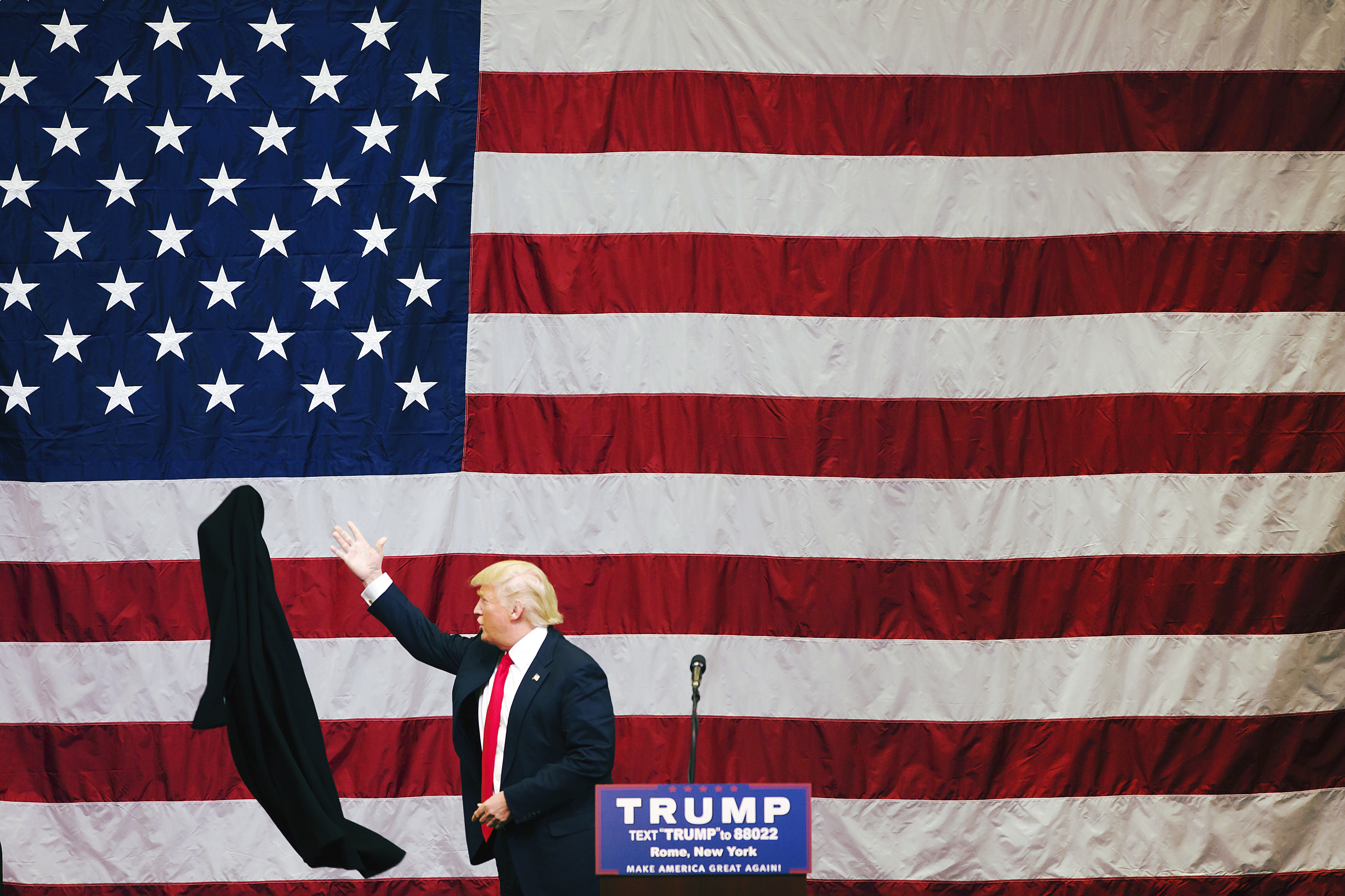 Donald Trump tosses his coat aside during a fly-in campaign stop at the Griffiss International Airport in Rome, N.Y., on April 12, 2016.
