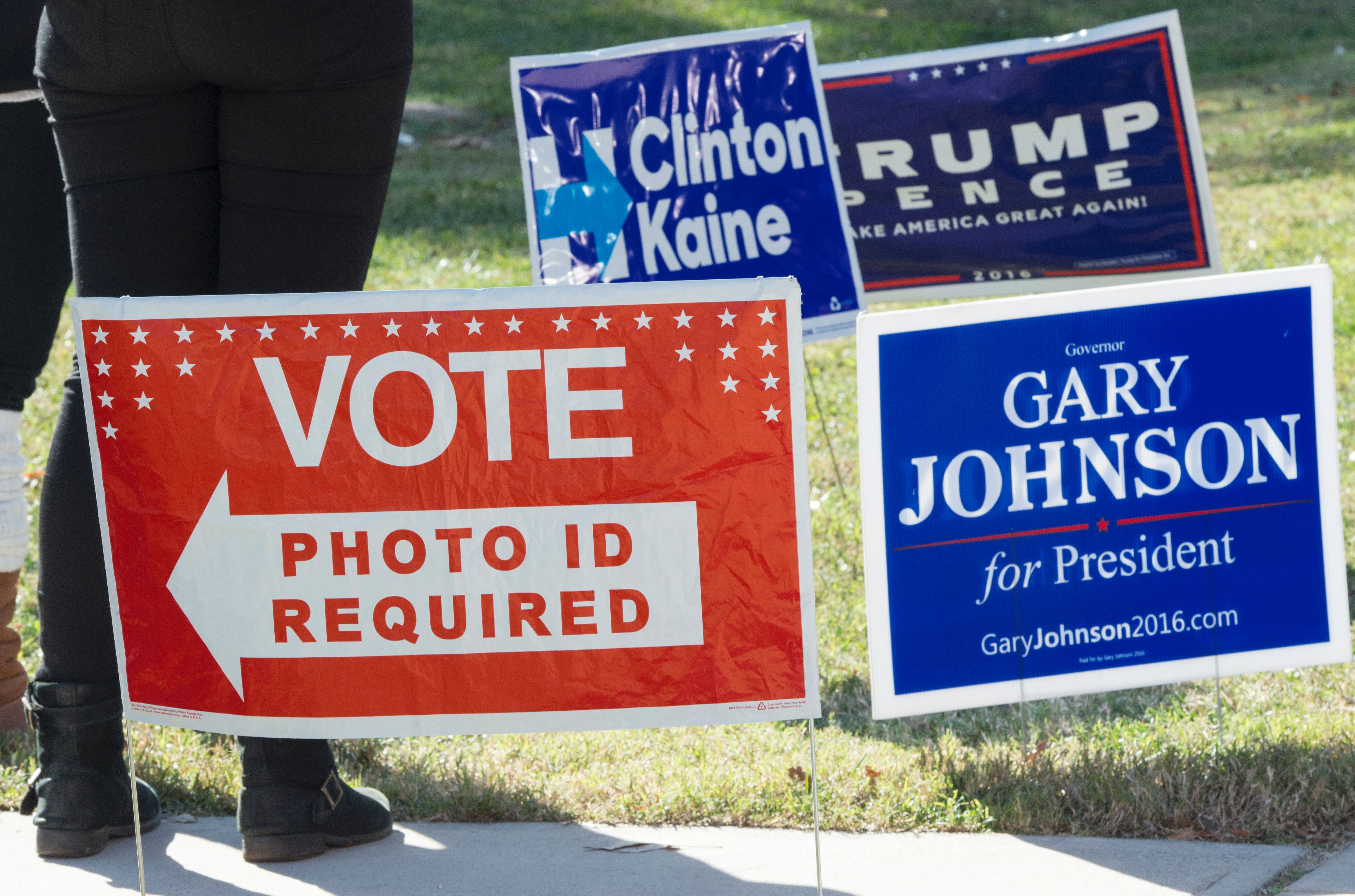 Signs are seen on a lawn near a US polling place in Arlington, Virginia, November 8, 2016.