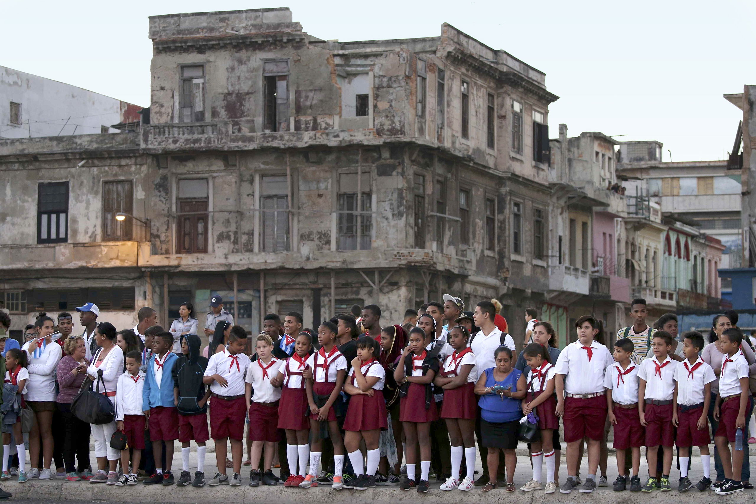 Schoolgirls in Havana on Nov. 30 await passage of the military vehicles carrying Castro's ashes on a three-day journey to Santiago, Cuba