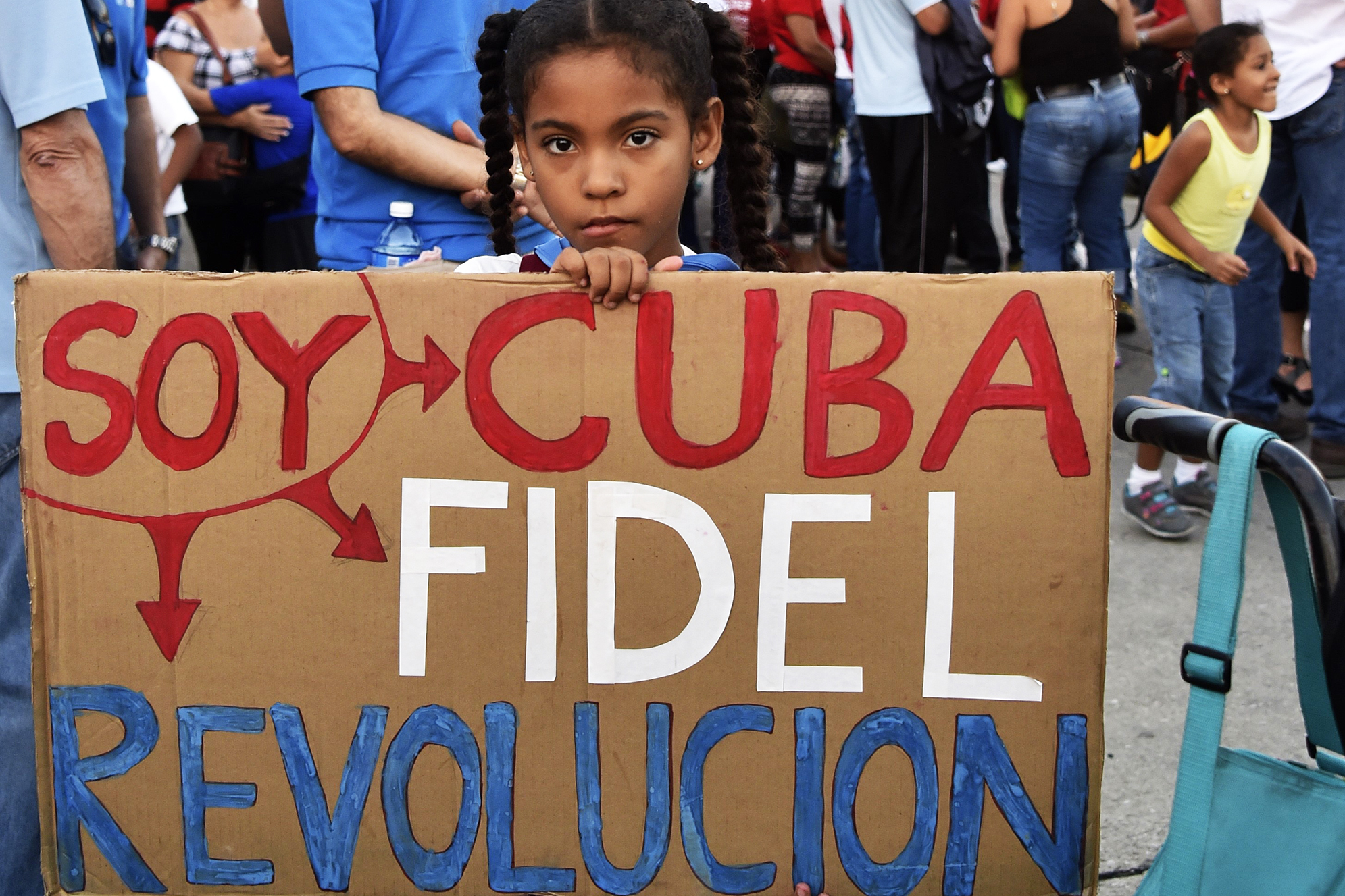 A girl holds a sign reading  I am Cuba, Fidel, Revolution  as Cubans gather at Revolution Square to pay homage to Fidel Castro in Havana, on Nov. 29, 2016.