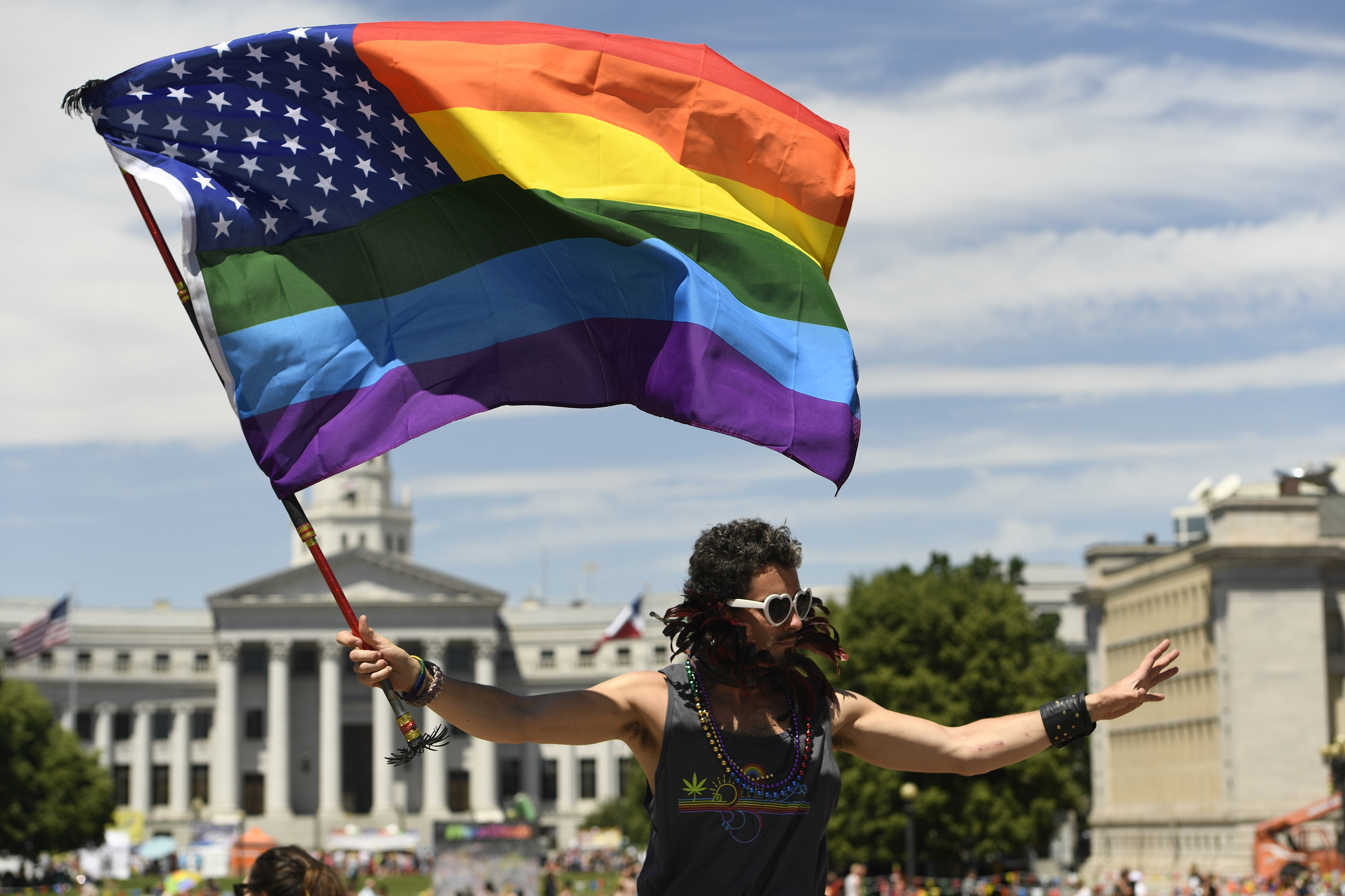 A man known as Mister Mischievous flies a Rainbow flag mixed with an American flag at Civic Center Park during the annual Denver PrideFest festivities in Denver on June 19, 2016.