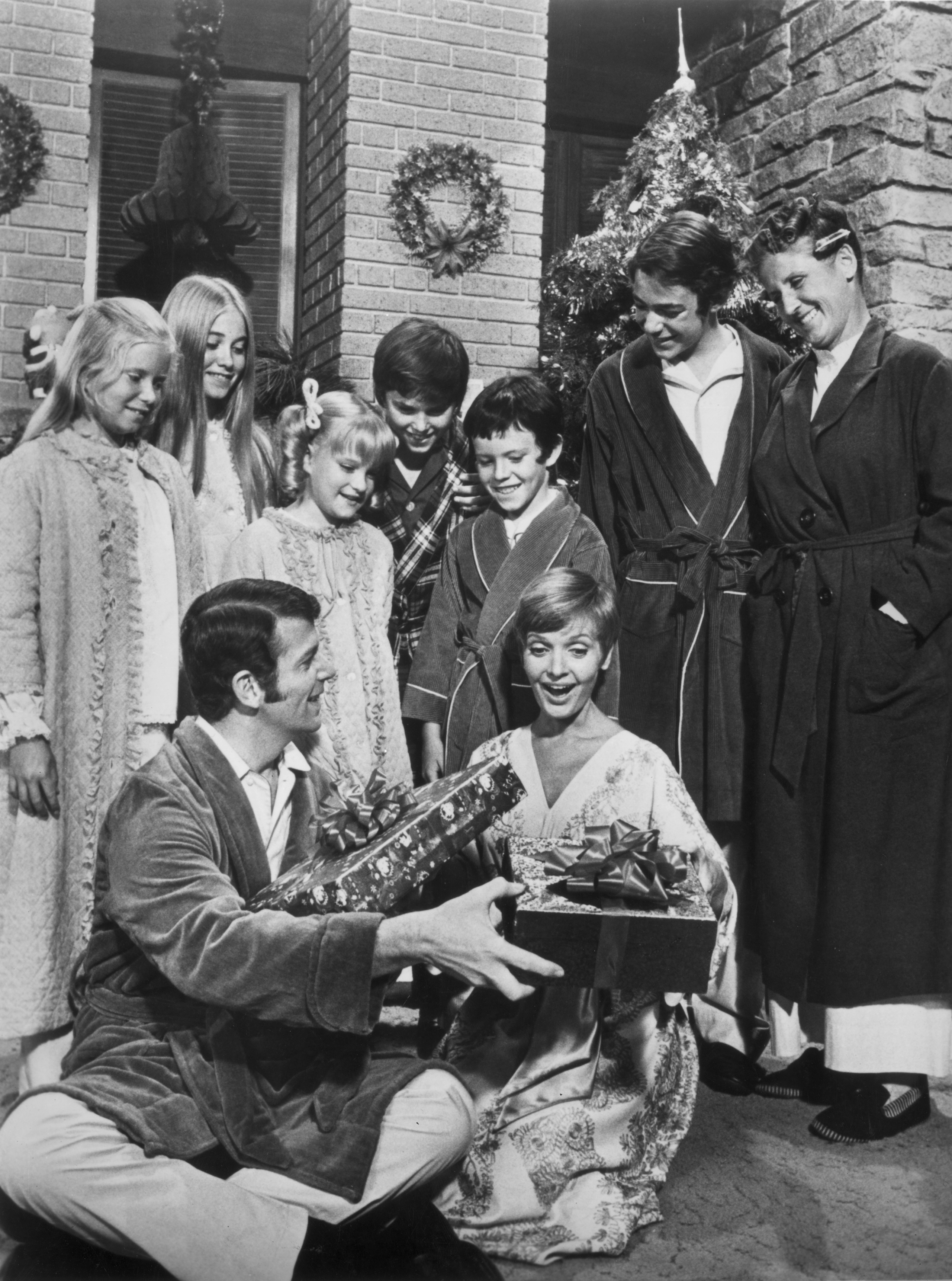 The cast of the television series 'The Brady Bunch' stands and watches  Robert Reed and Florence Henderson exchange wrapped Christmas presents during the episode 'A Very Brady Christmas'.