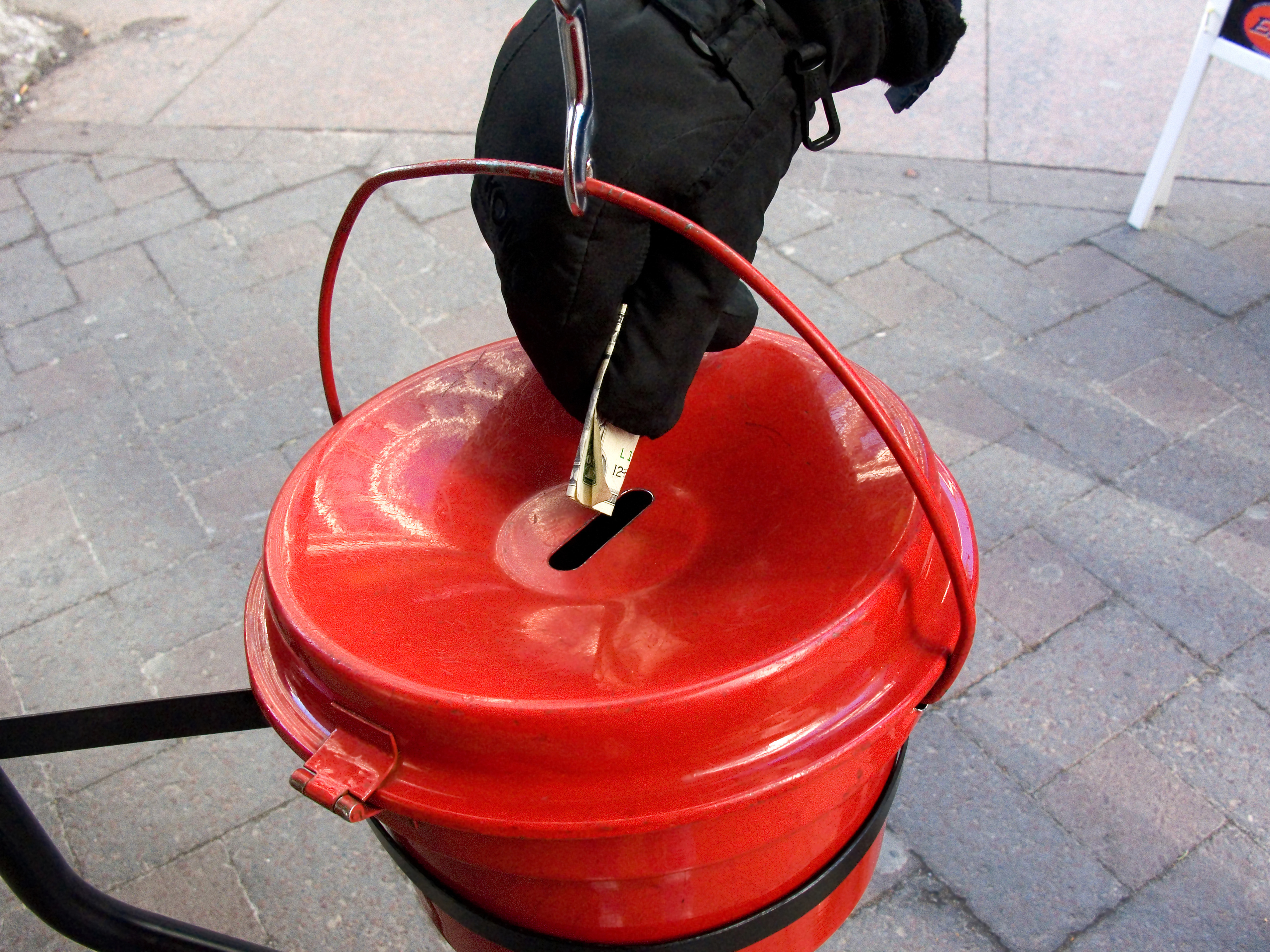 Person putting money into a Salvation Army kettle.