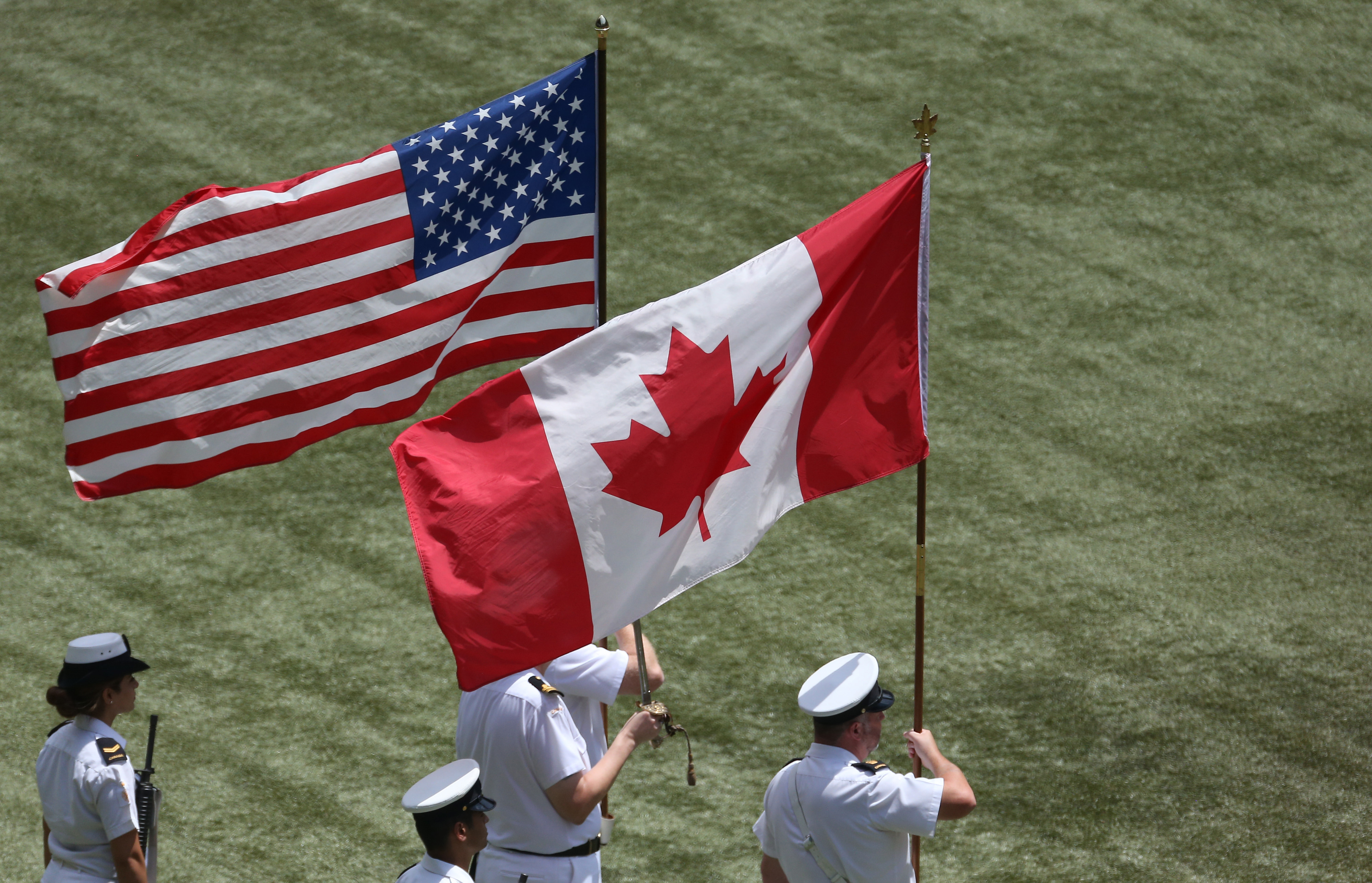 The color guard holds an American flag and a Canadian flag during a pre-game ceremony on Canada Day before the start of the Toronto Blue Jays MLB game against the Milwaukee Brewersat Rogers Centre in Toronto, Ontario, Canada, on July 1, 2014.