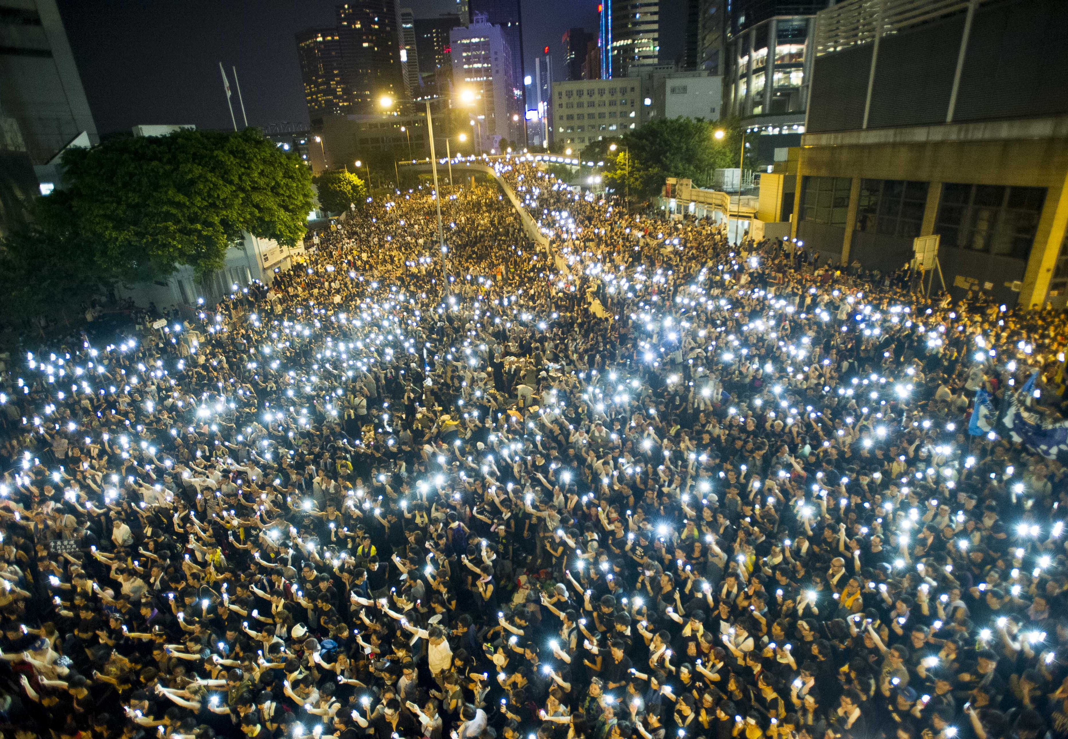 Protestors and student demonstrators hold up their cell phones in a display of solidarity during a protest outside the headquarters of Legislative Council in Hong Kong on Sept. 29, 2014