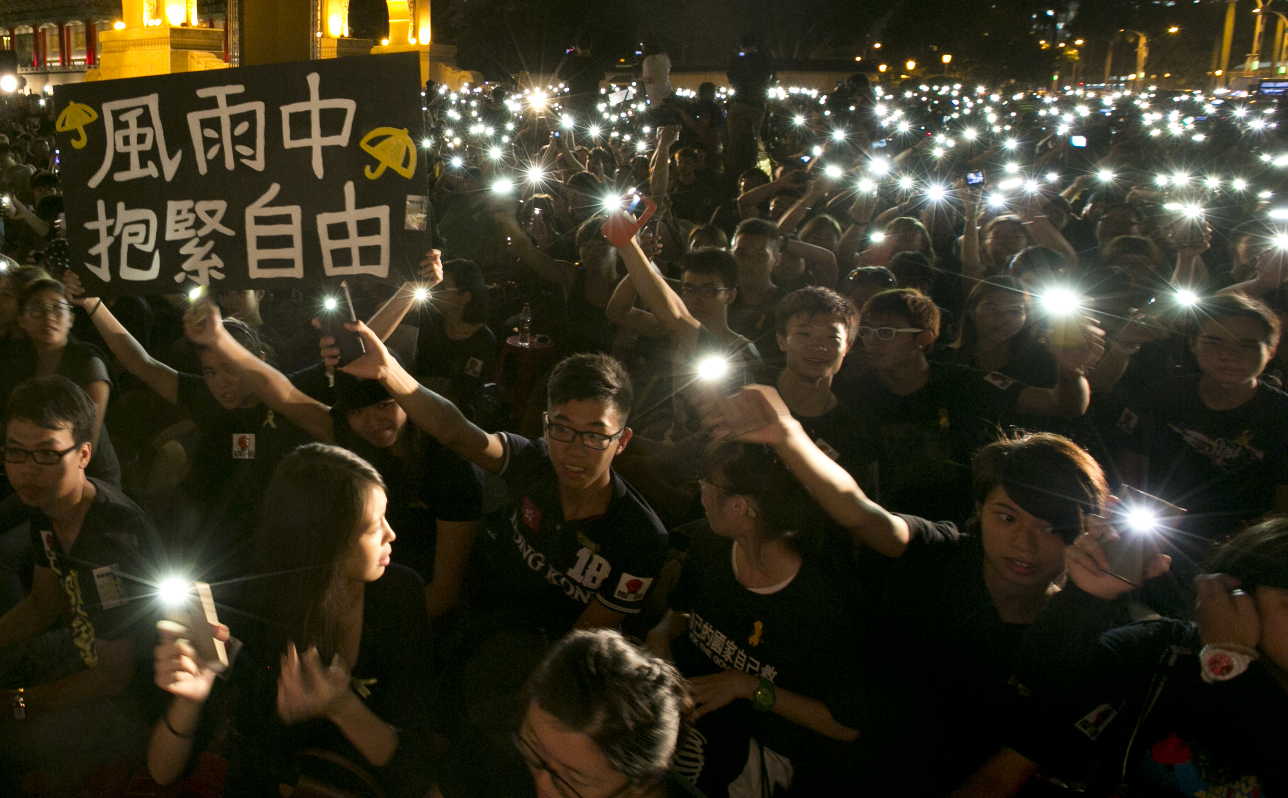 Hundreds of Taiwanese students raise their cell phones with one sign reading  Hold On to Freedom in the Rain  on Oct. 1, 2014, in front of Liberty Square in Taipei to show support for Hong Kong pro-democracy rallies