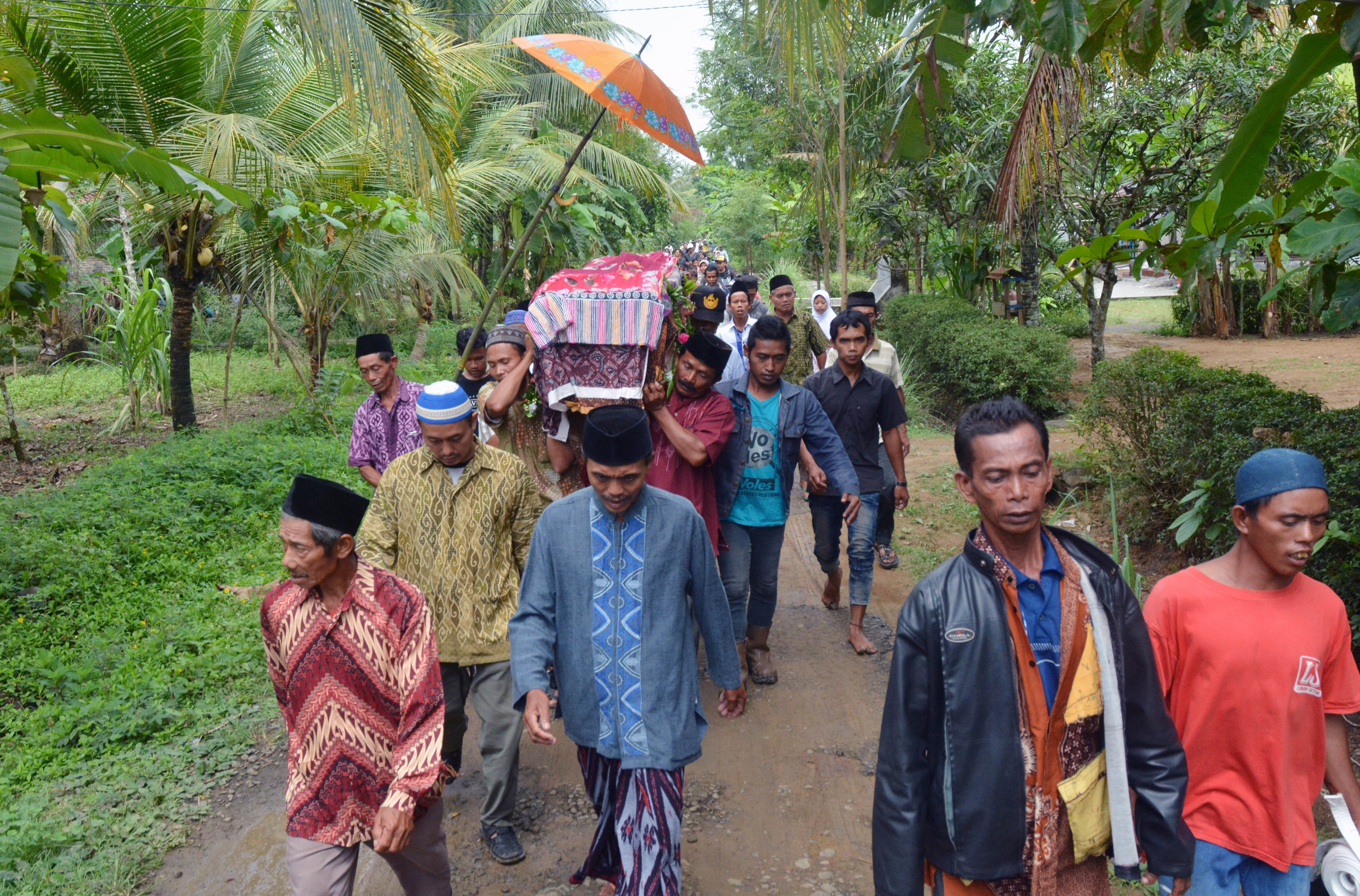 Relatives and villagers carry the coffin of Sumarti Ningsih, one of two Indonesian women murdered by British banker Rurik Jutting in Hong Kong, during her funeral at Gandrungmangu village, in Cilacap, Indonesia's Central Java province, on Nov. 12, 2014