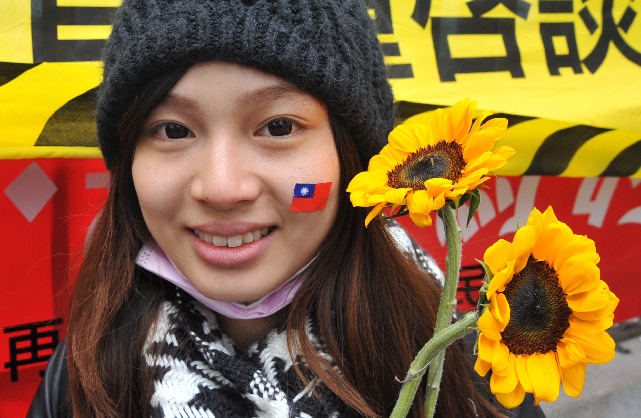 An activist holds sunflowers and wears a sticker of Taiwan's national flag on her face in support of student protesters occupying the parliament building in Taipei on March 21, 2014