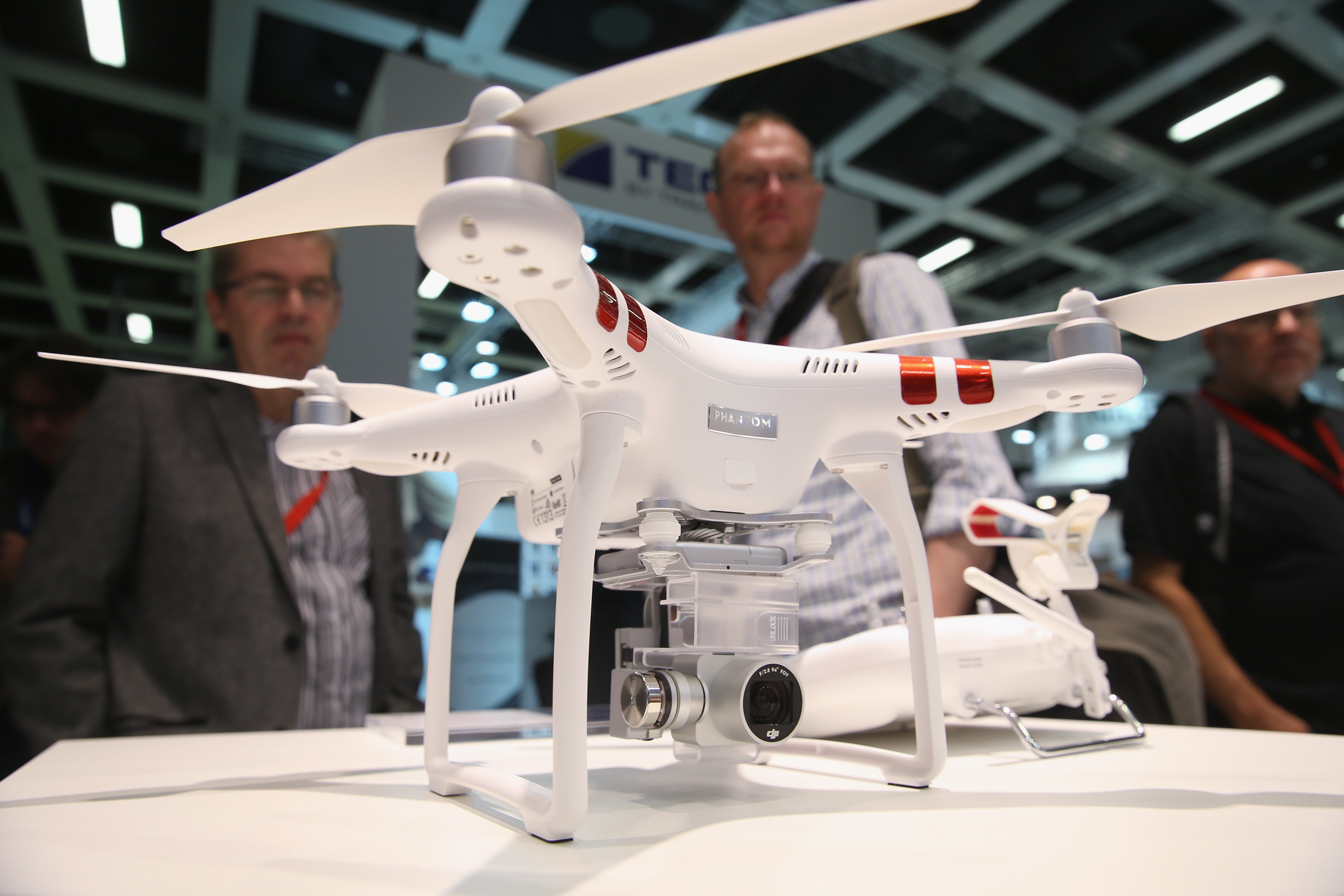 Visitors look at a Phantom 3 Standard quadcopter drone at the DJI stand during a press day at the 2015 IFA consumer electronics and appliances trade fair on September 3, 2015 in Berlin, Germany.