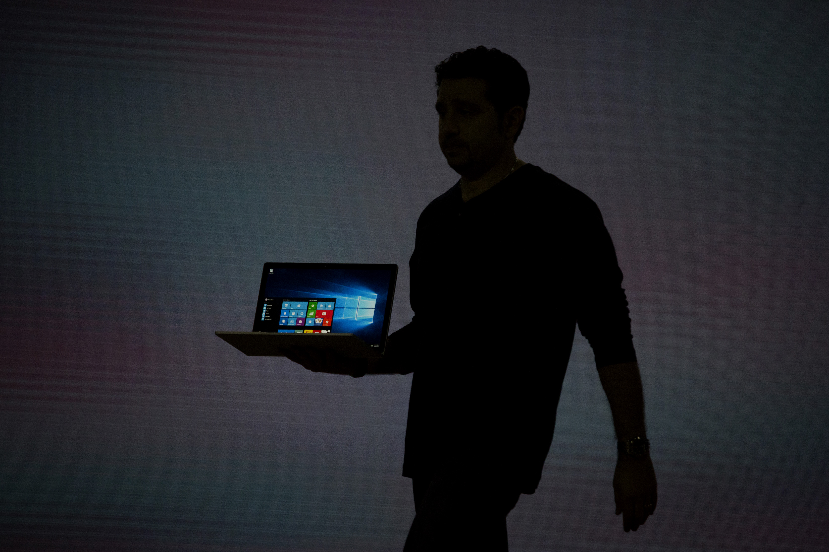 The silhouette of Panos Panay, corporate vice president of Microsoft Corp. Surface, is seen as he unveils the new Microsoft Surface Book laptop during the Windows 10 Devices event in New York, U.S., on Tuesday, Oct. 6, 2015.