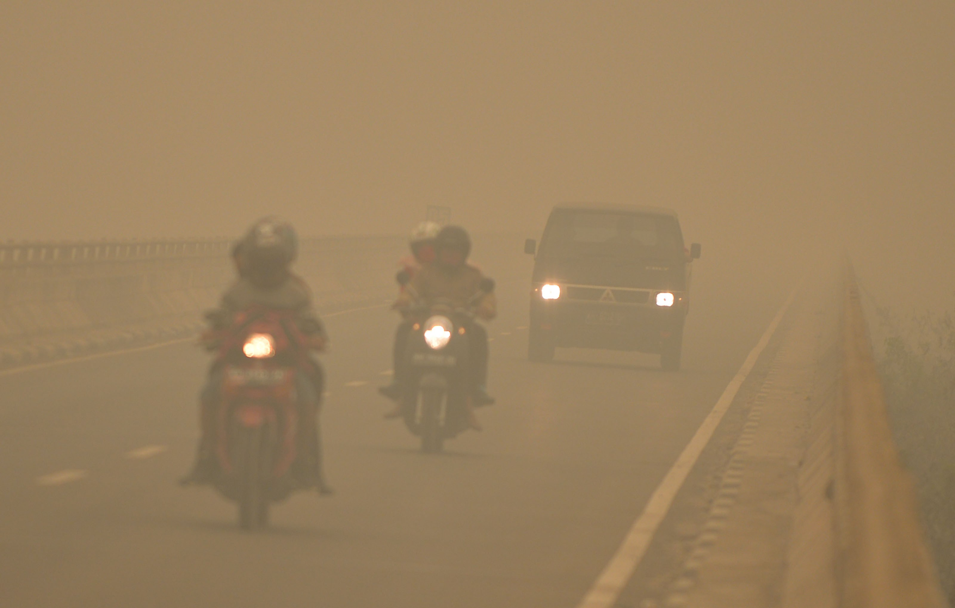 Commuters drive through thick haze in Tumbang Nusa, Central Kalimantan, on Oct. 25, 2015.