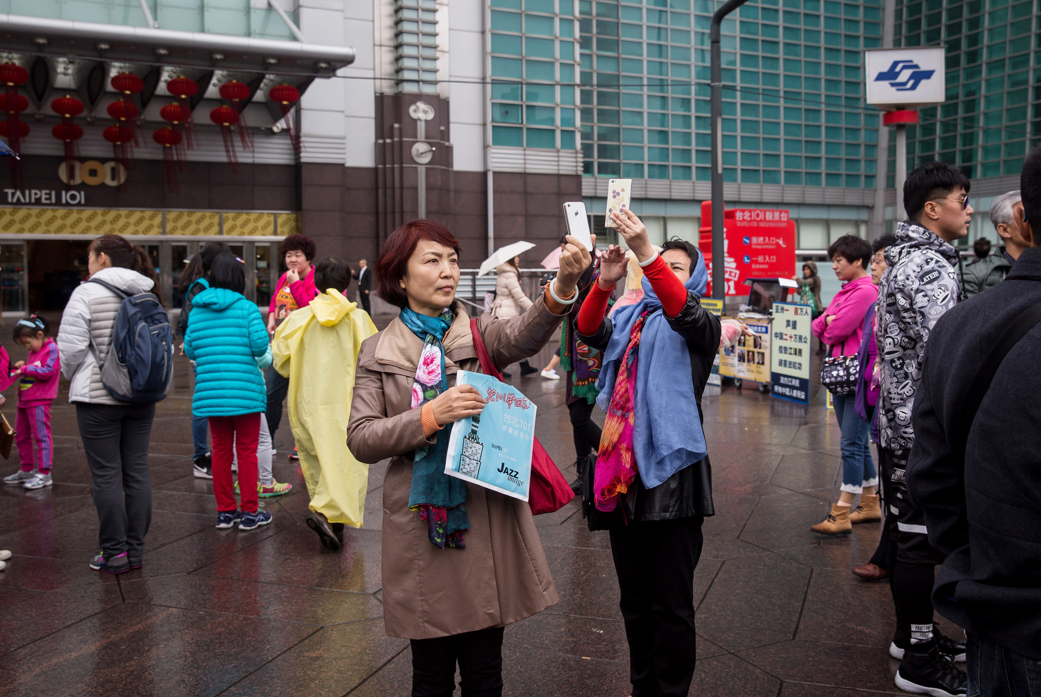 Tourists take photographs using smartphones outside the Taipei 101 building in Taipei on Jan. 13, 2016