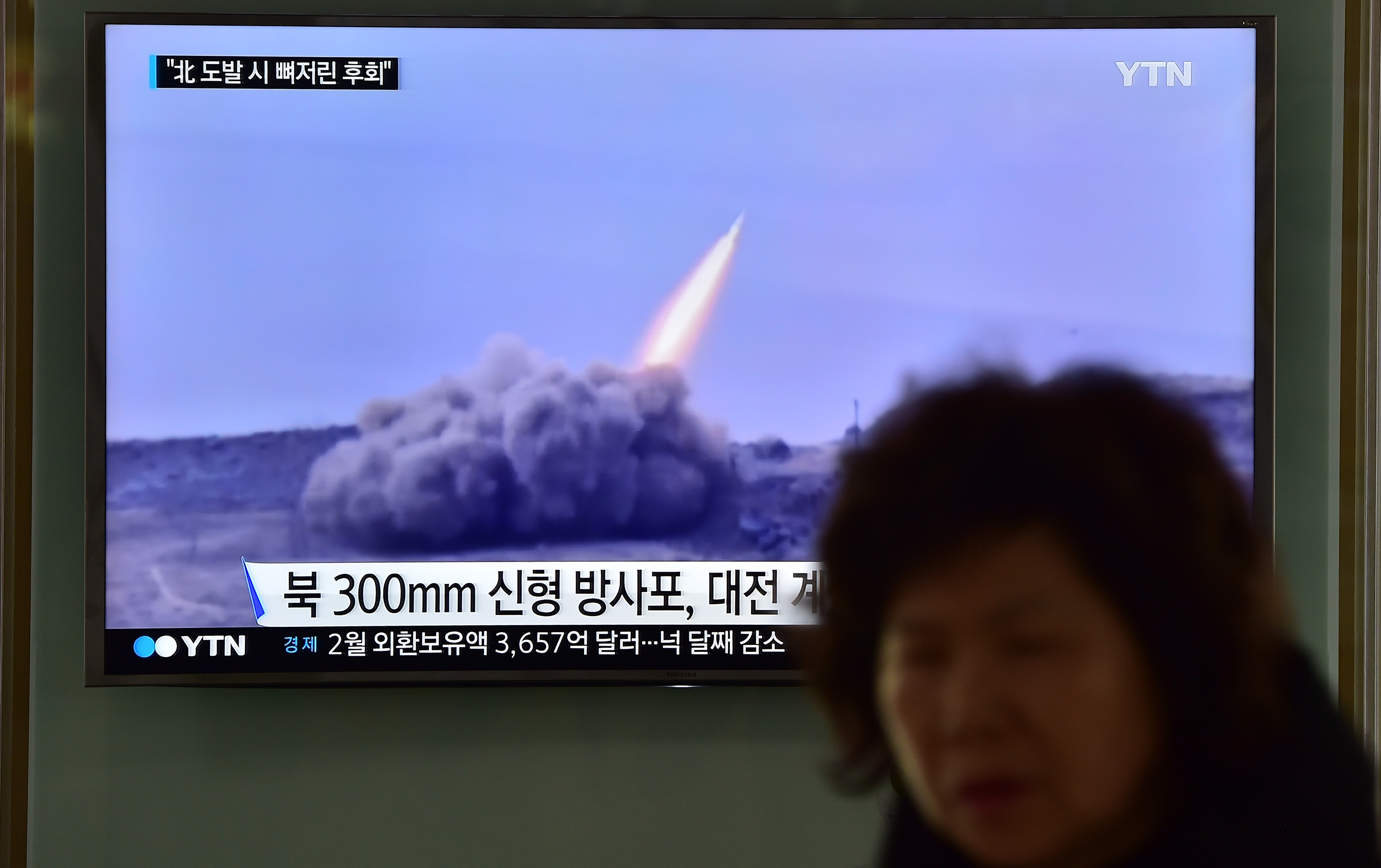 A woman walks past a public television screen, showing file footage of a North Korean missile, at a railway station in Seoul on March 4, 2016
