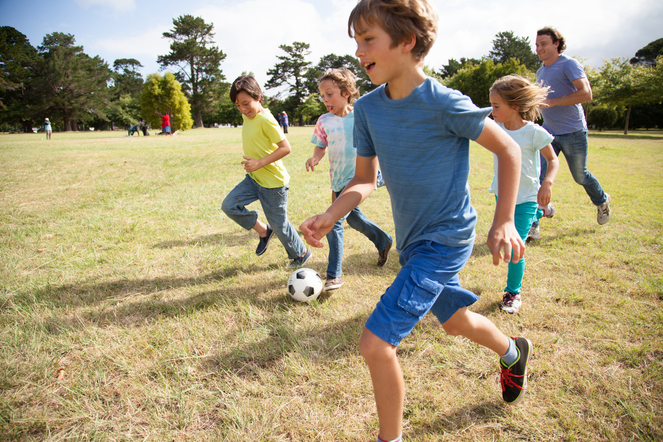Children, aged 9-10, running together with a soccer ball in a park