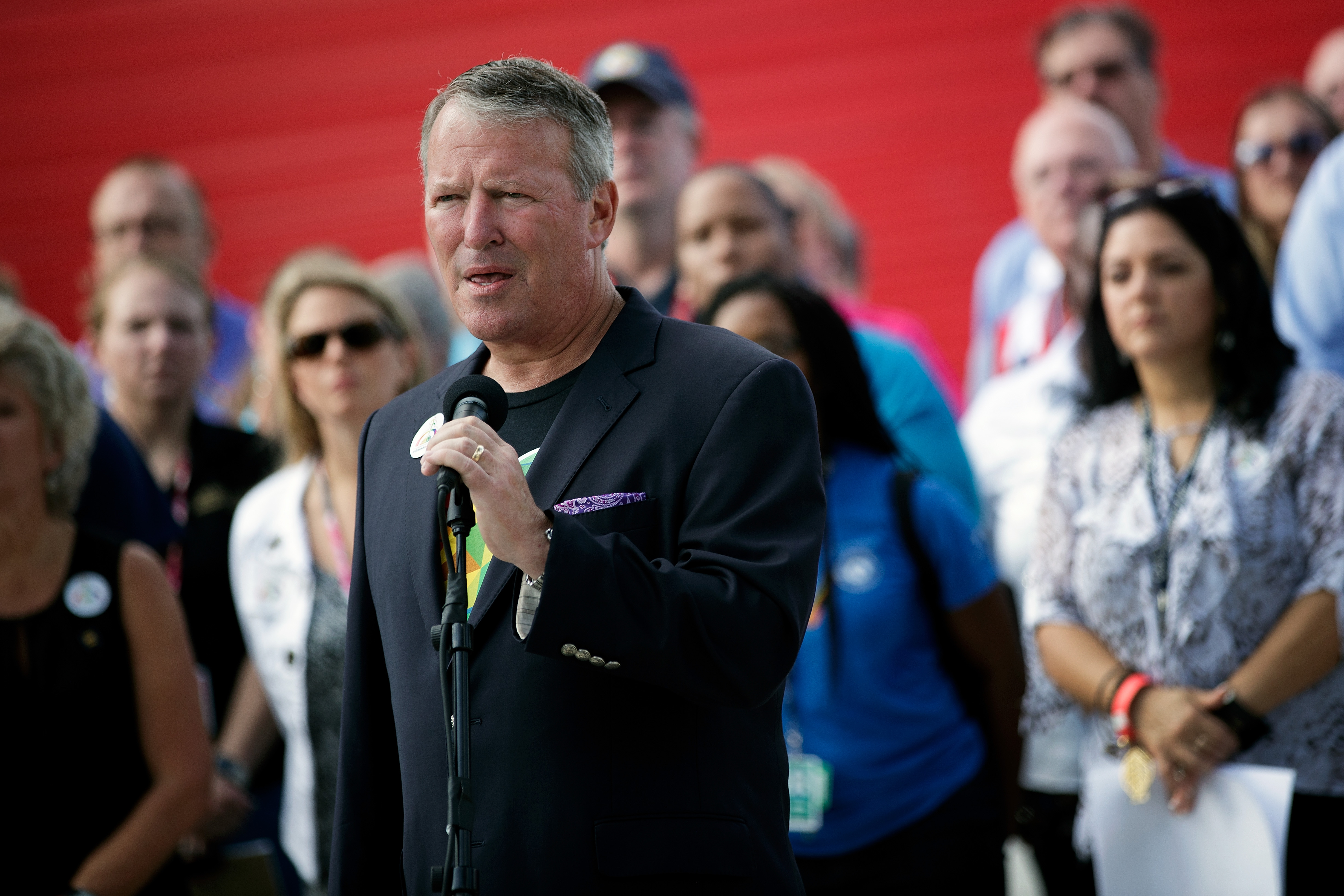 Surrounded by members of federal, state and local agencies, Orlando Mayor Buddy Dyer speaks at a press conference to provide an update on the assistance being provided to victims' families at the Orland Family Assistance Center, at Camping World Stadium, June 17, 2016 in Orlando, Florida.