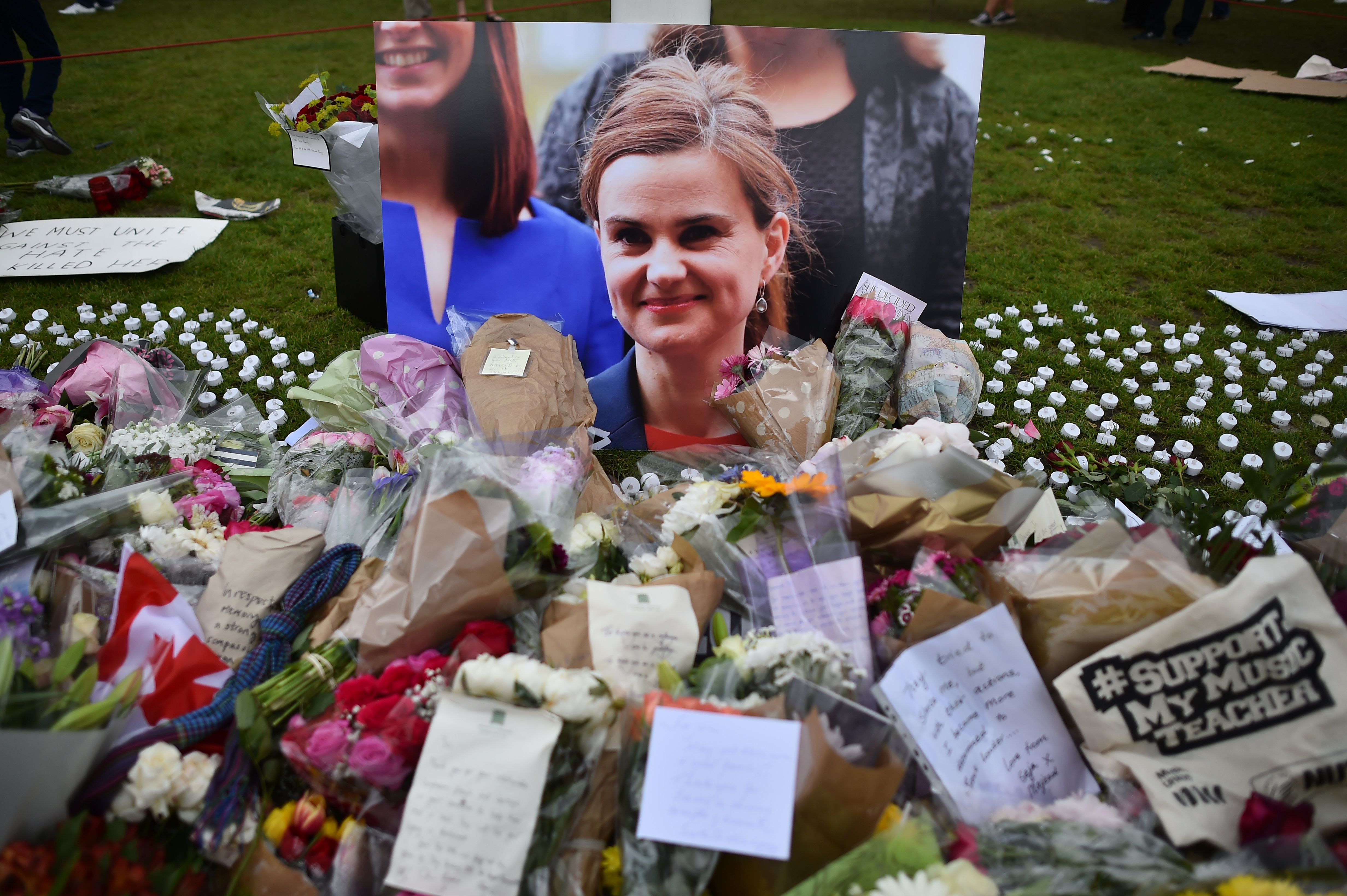 Flowers and tributes are piled in remebrance against a photograph of slain Labour MP Jo Cox in Parliament Square central London on June 18, 2016.  Thomas Mair has been found guilty of Cox's murder.
