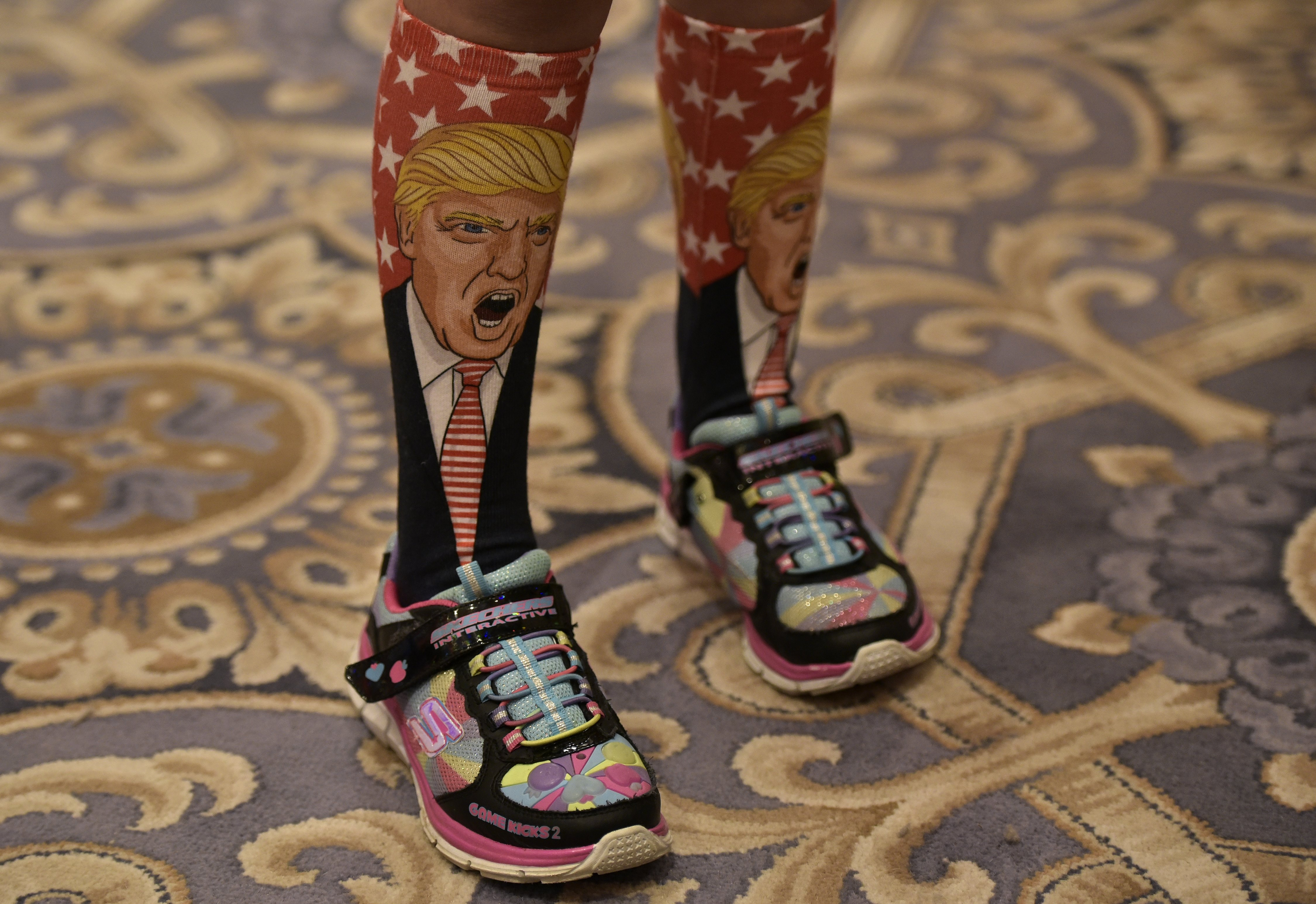 A young supporter wears socks with the image of Donald Trump ahead of his press conference at the Trump International Hotel, in Washington, DC, on Sept. 16, 2016.