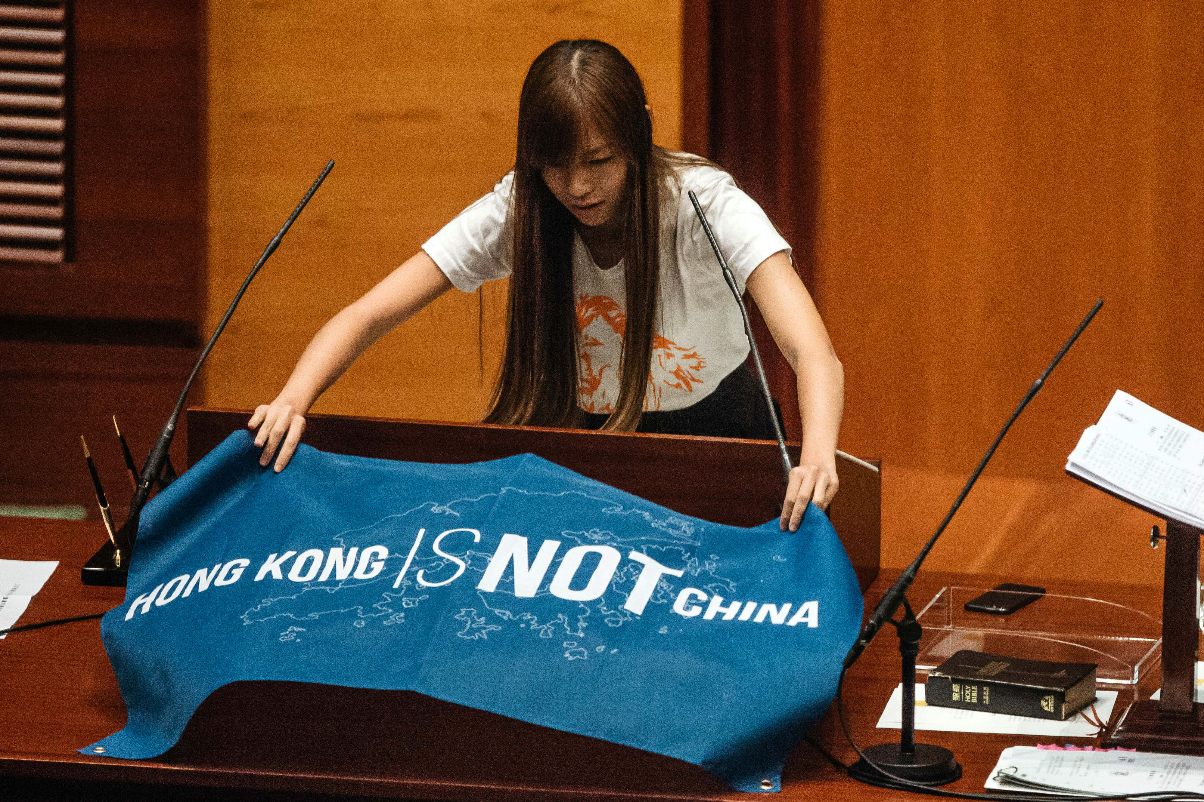 Yau Wai-ching, an incoming lawmaker and member of Youngspiration, unfurls a banner that reads  Hong Kong Is Not China  in the chamber of the Legislative Council in Hong Kong on Oct. 12, 2016
