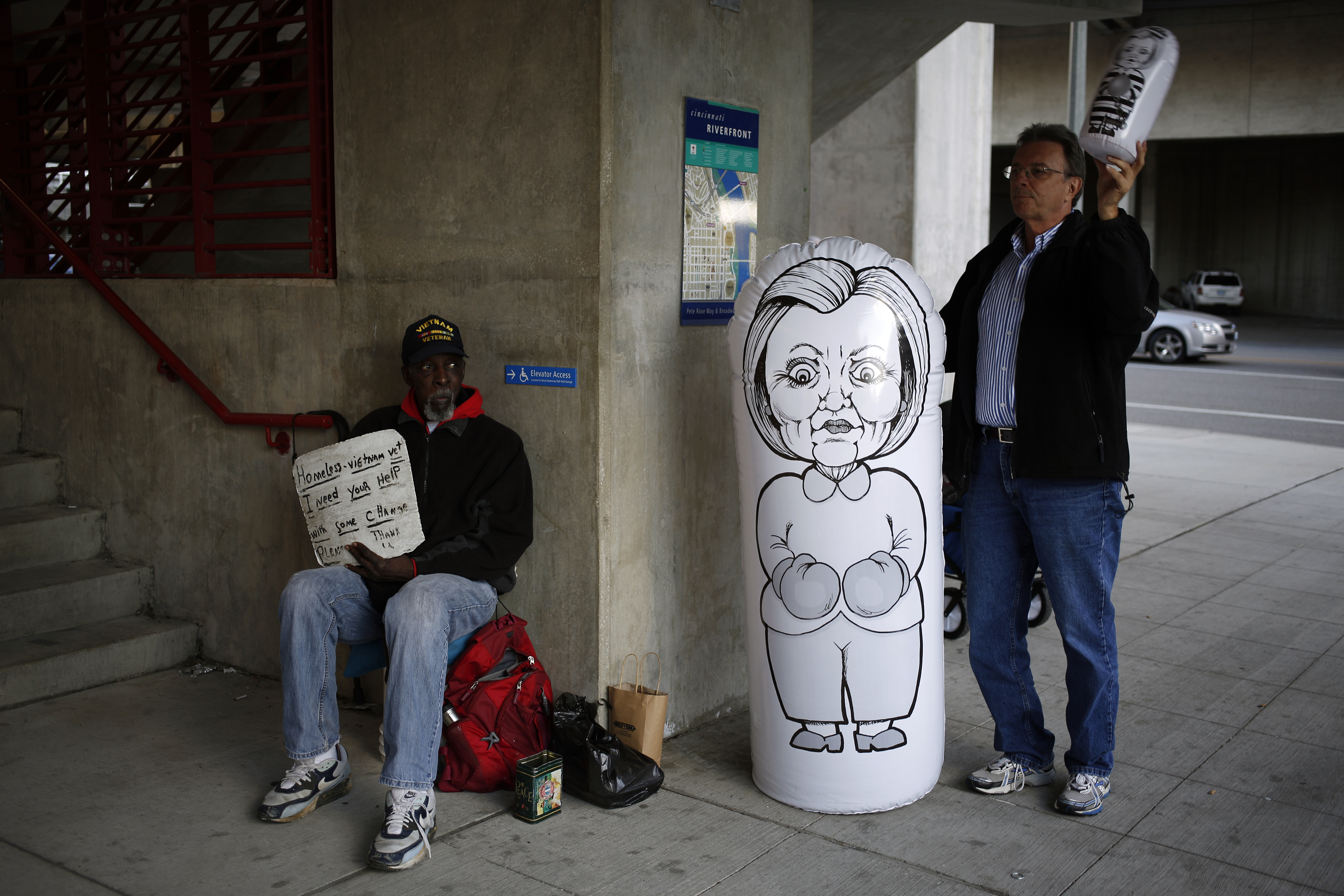 A vendor sells an inflatable punching bag bearing a caricature of Hillary Clinton next to a man begging for money outside a campaign event for Donald Trump in Cincinnati, Ohio, on Oct. 13, 2016.