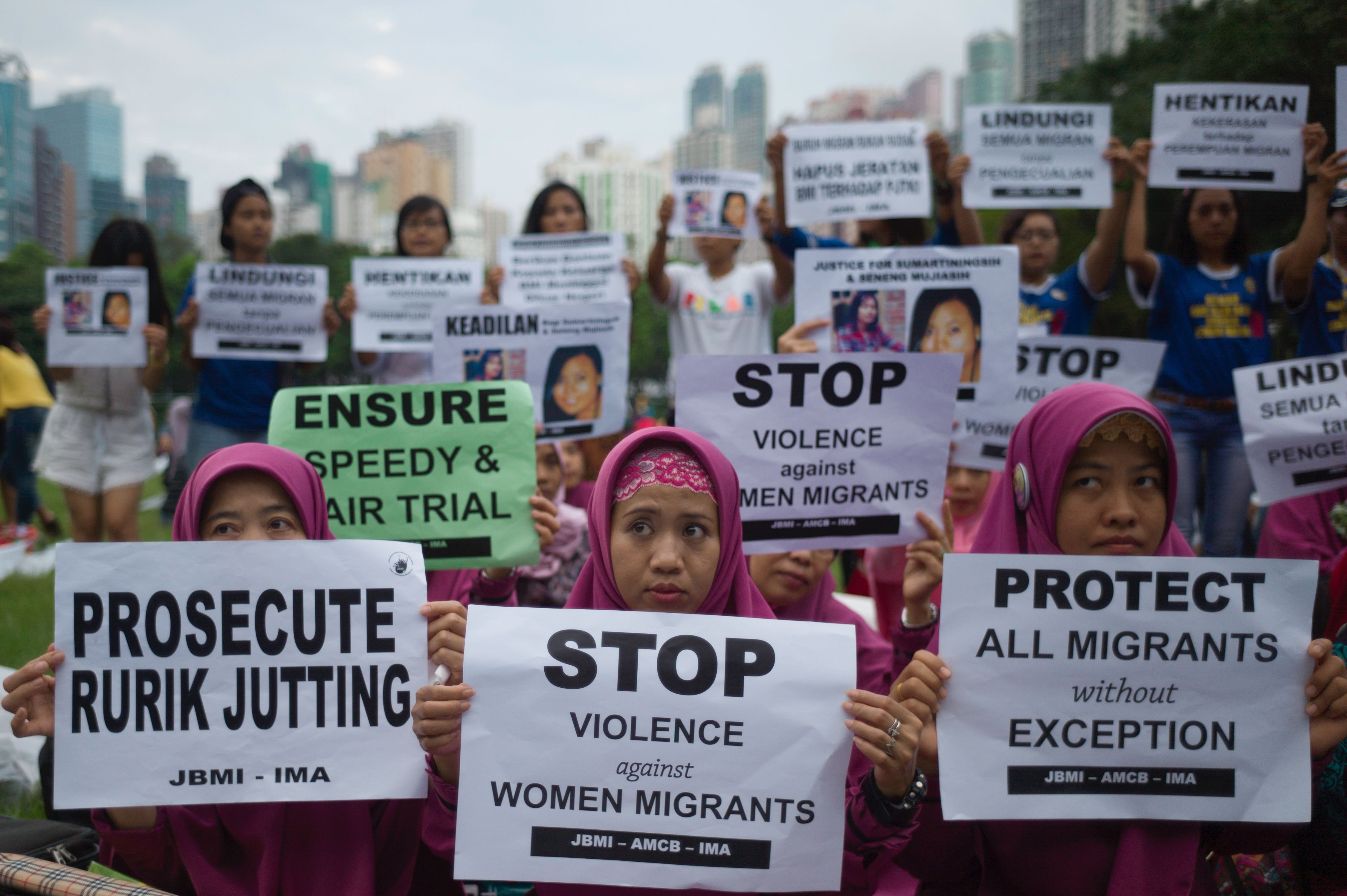 Indonesian migrant workers hold up placards during a vigil for slain colleagues Seneng Mujiasih and Sumarti Ningsih on the eve of the murder trial for British banker Rurik Jutting, in Hong Kong's Victoria Park on Oct. 23, 2016