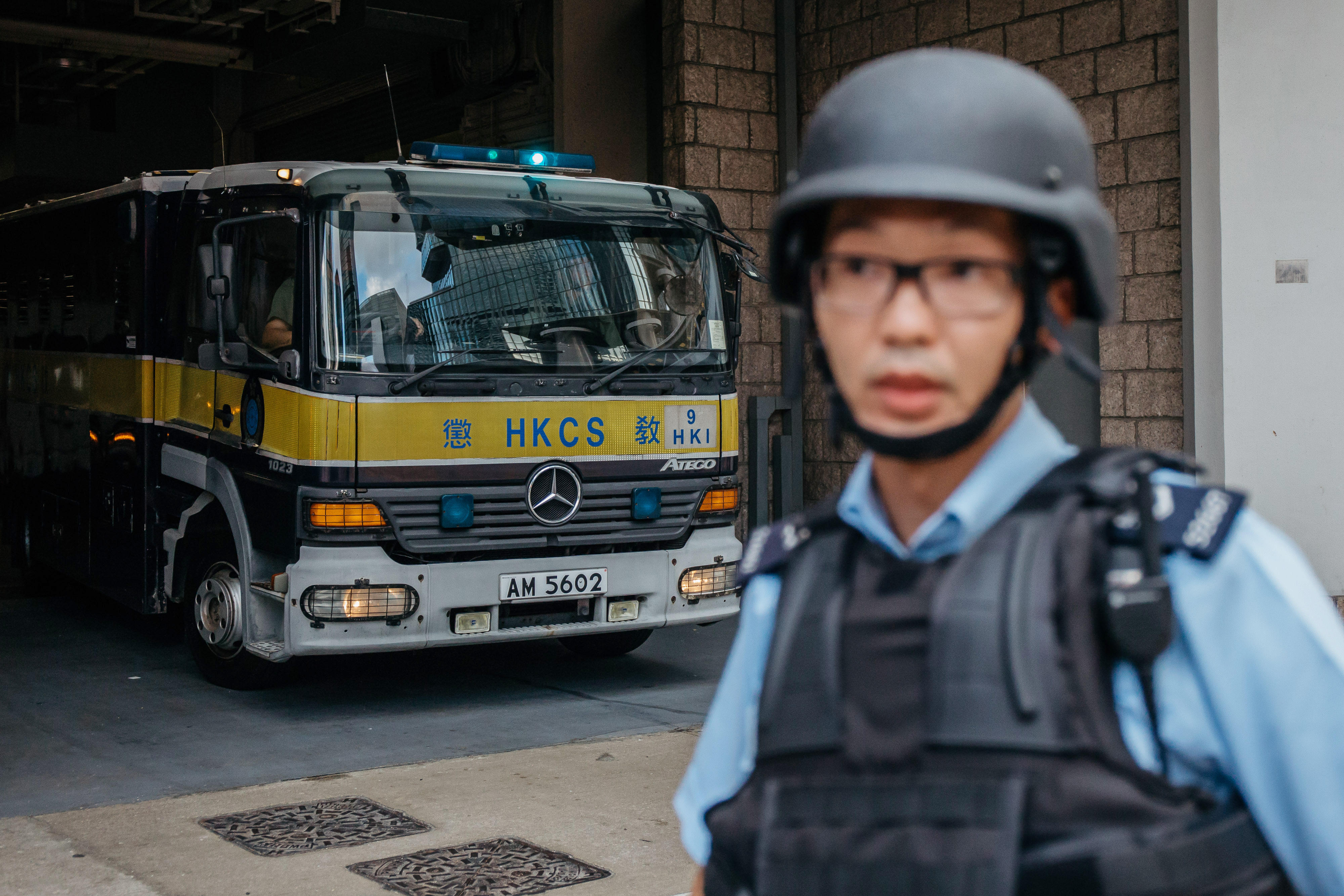 A police officer stands guard as a prison vehicle escorting Rurik Jutting, a former Bank of America Merrill Lynch employee, leaves the High Court in Hong Kong on Oct. 24, 2016