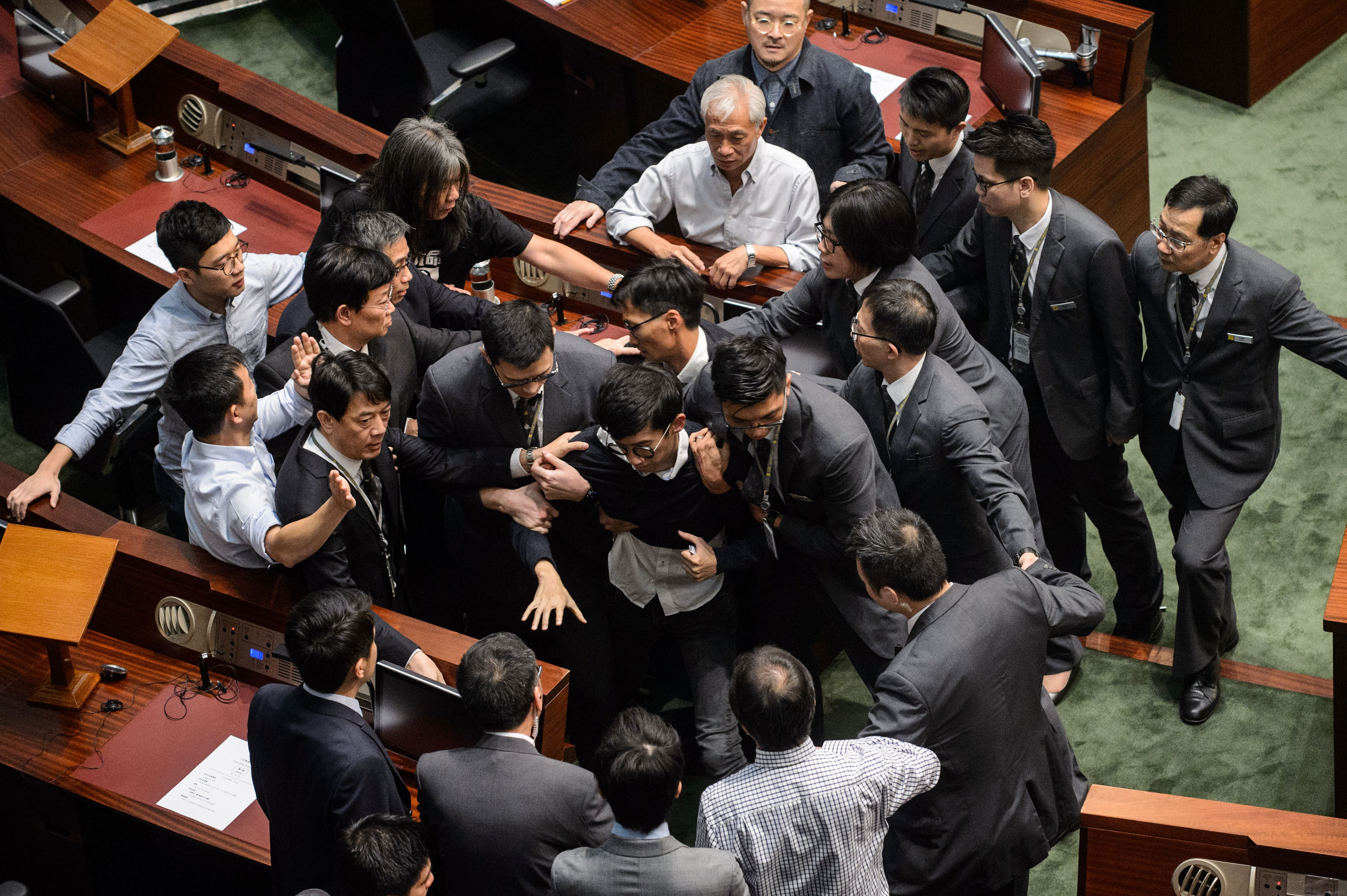 Newly elected lawmaker Sixtus  Baggio  Leung, center, is restrained by security after attempting to read out his oath of office at the Legislative Council in Hong Kong on Nov. 2, 2016