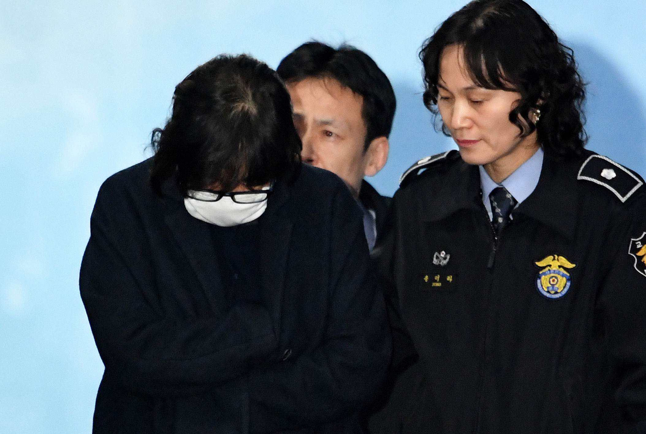 Choi Soon-Sil, front left, the woman at the heart of a lurid political scandal engulfing South Korea's President Park Geun-hye, is escorted following her formal arrest, from the Central District Court in Seoul on Nov. 3, 2016
