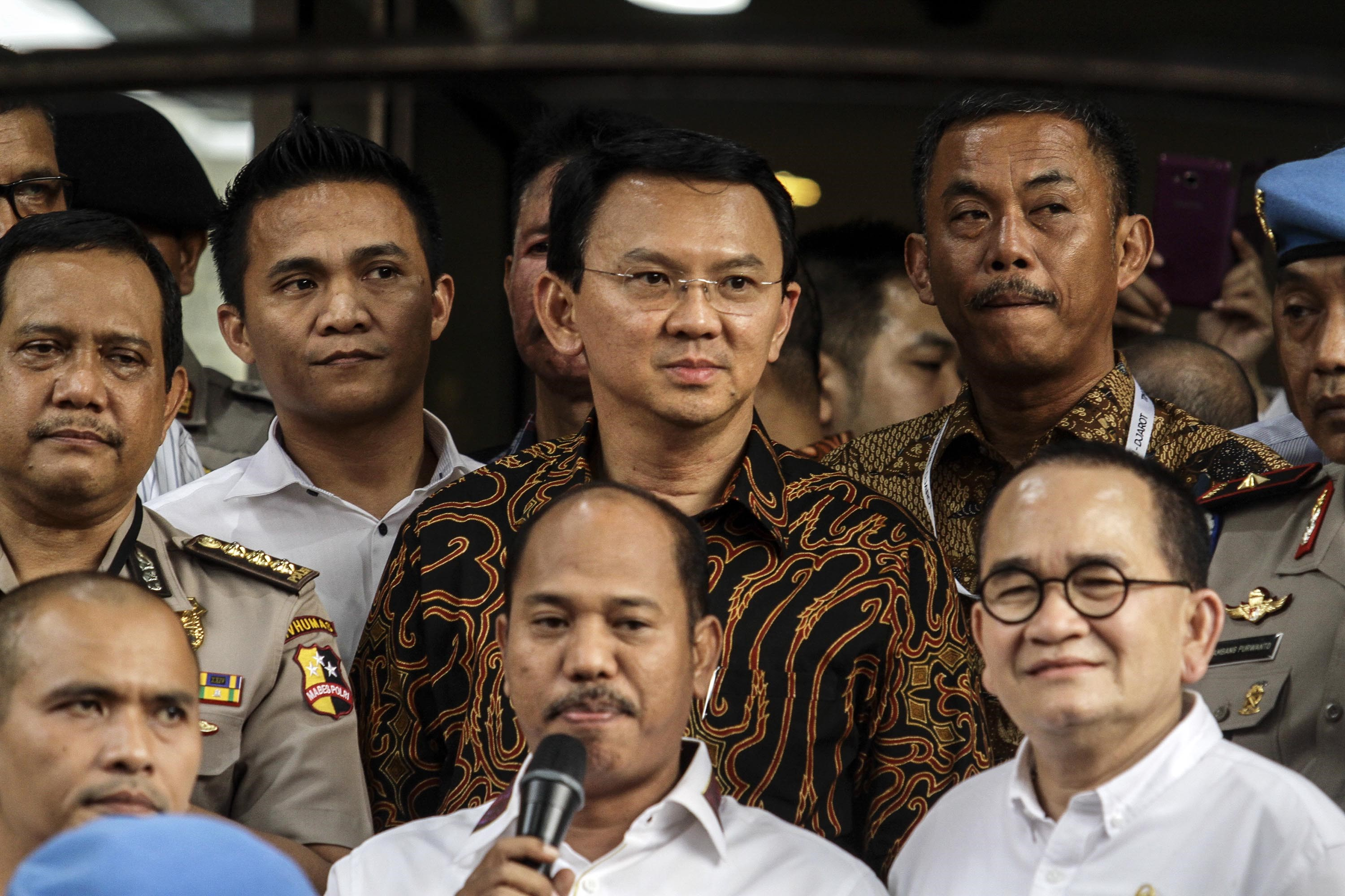 Jakarta's Governor Basuki Tjahaja Purnama, center, in a batik shirt, faces journalists after investigation by the police at the police headquarters in Jakarta on Nov. 7, 2016