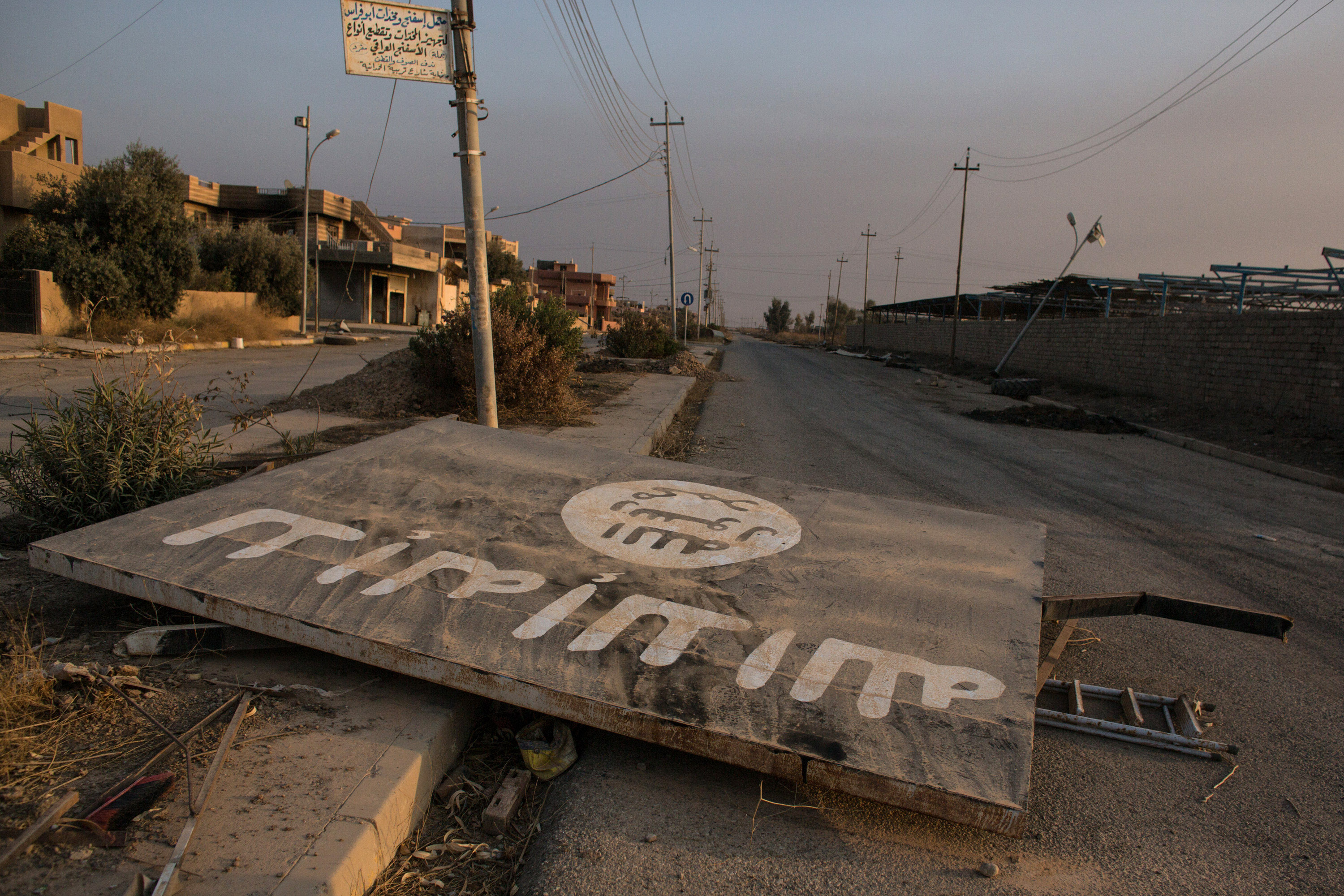 An ISIL billboard is seen destroyed in the middle of the road Qaraqosh, Iraq on Nov. 8, 2016
